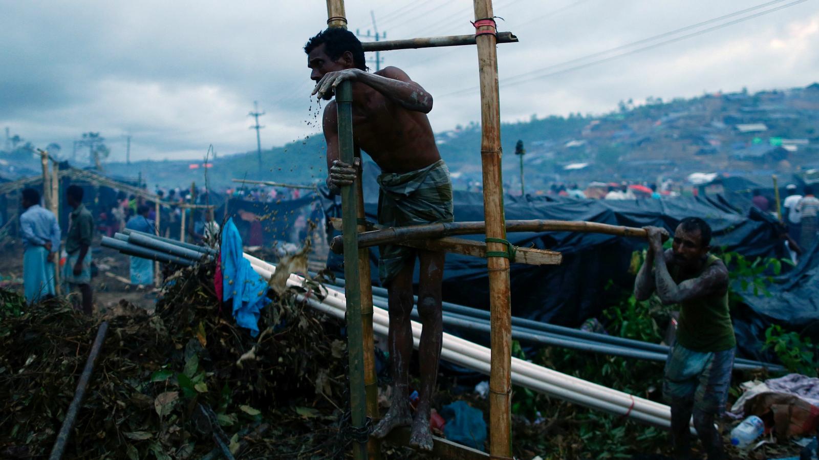 Rohingya refugees manually drill a borewell at a camp in Cox's Bazar, Bangladesh