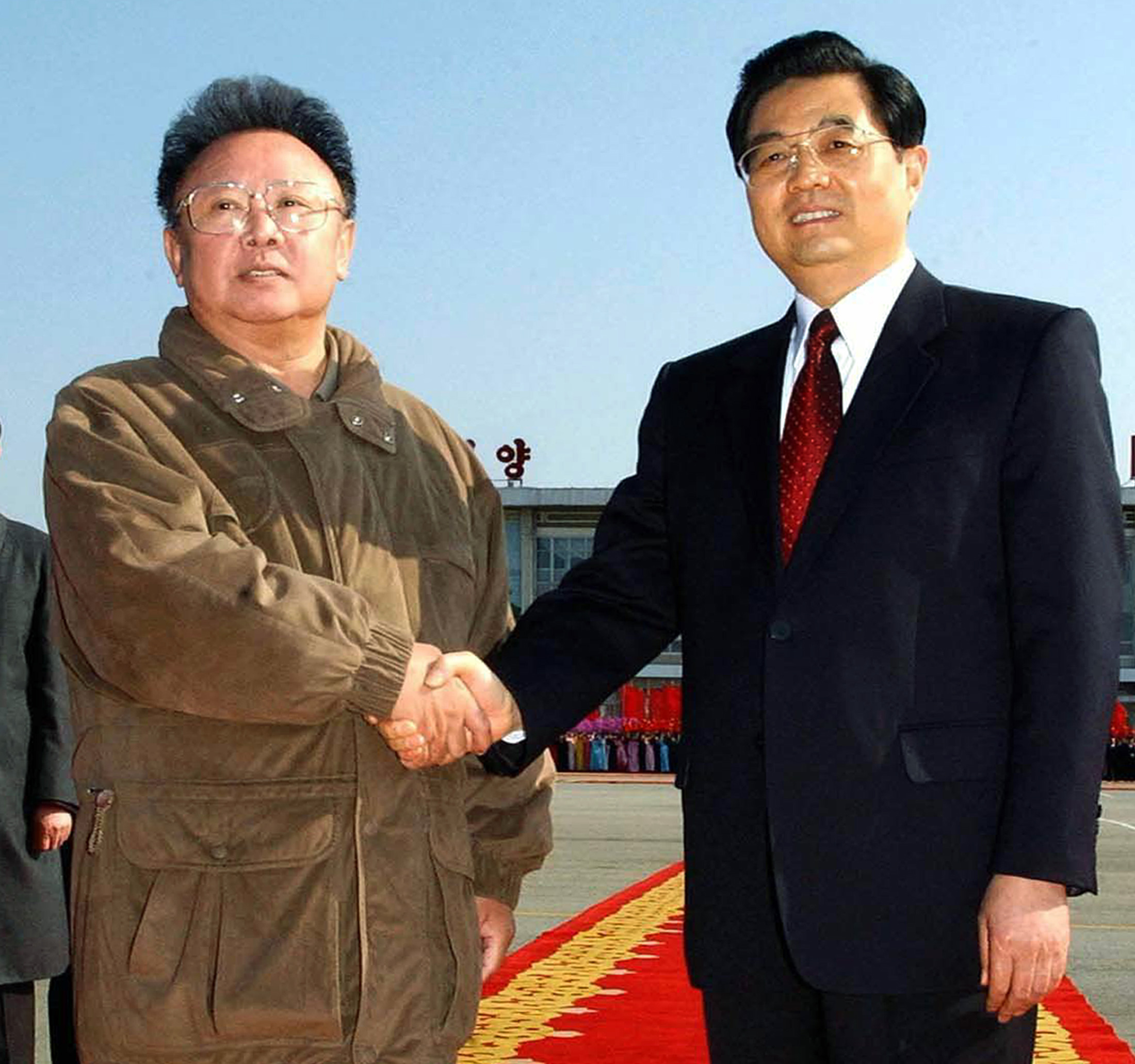 North Korean leader Kim Jong-il (L) shakes hands with Chinese President Hu Jintao as he sees off the Chinese leader on his departure from Pyongyang airport October 30, 2005, in this picture released by Korea News Service in Tokyo October 31, 2005. Hu was concluding an official visit to North Korea. JAPAN OUT REUTERS/Korea News Service - RP2DSFIICSAD