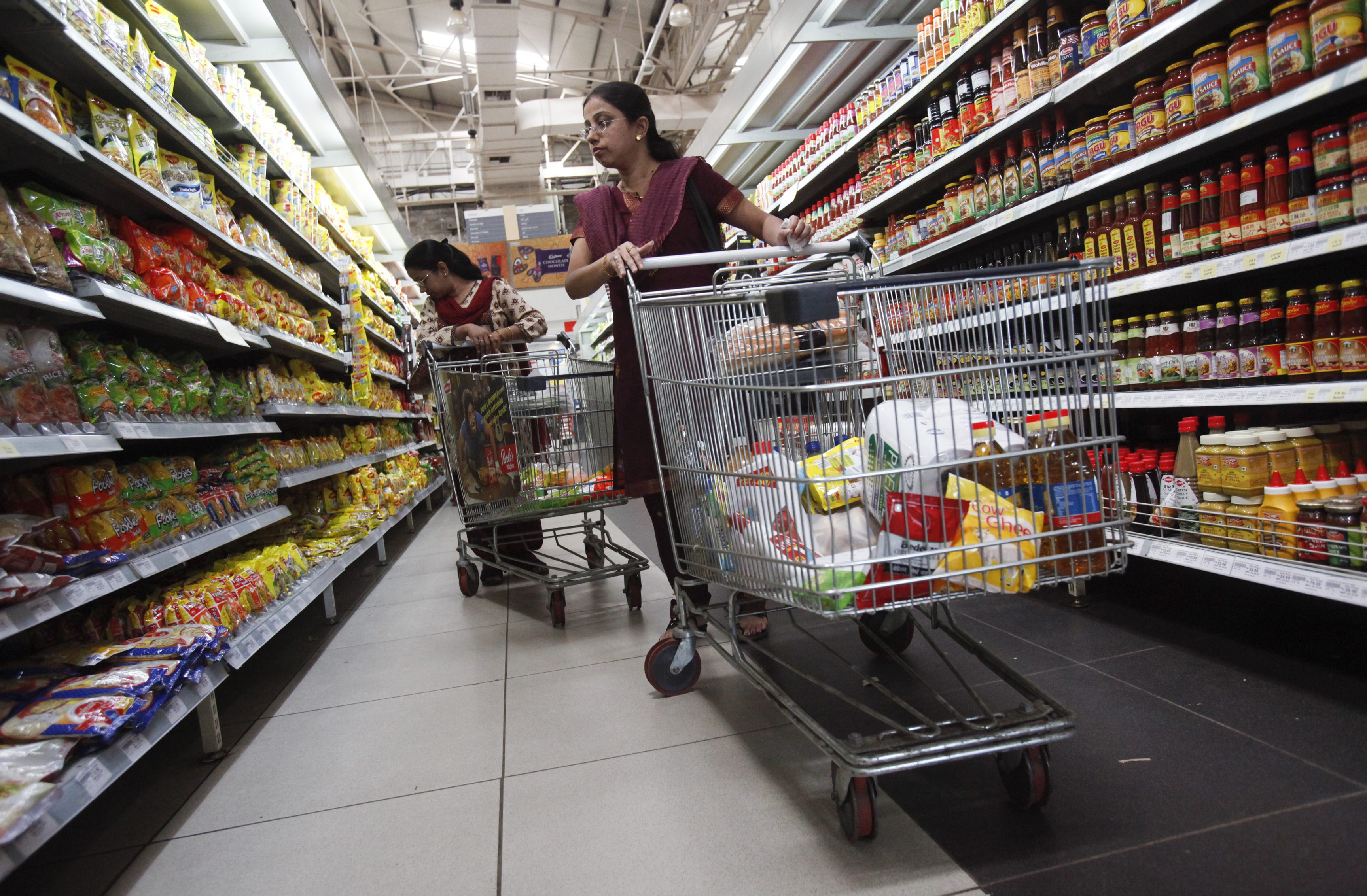 Women shop for instant noodles at a retail supermarket in Mumbai March 16, 2012. The Indian government played it safe in unveiling its 2012/13 budget on Friday, pledging reforms but setting only modest targets for trimming a ballooning fiscal deficit, disappointing bond market investors. REUTERS/Vivek Prakash (INDIA - Tags: BUSINESS POLITICS) - GM1E83G1NKM01