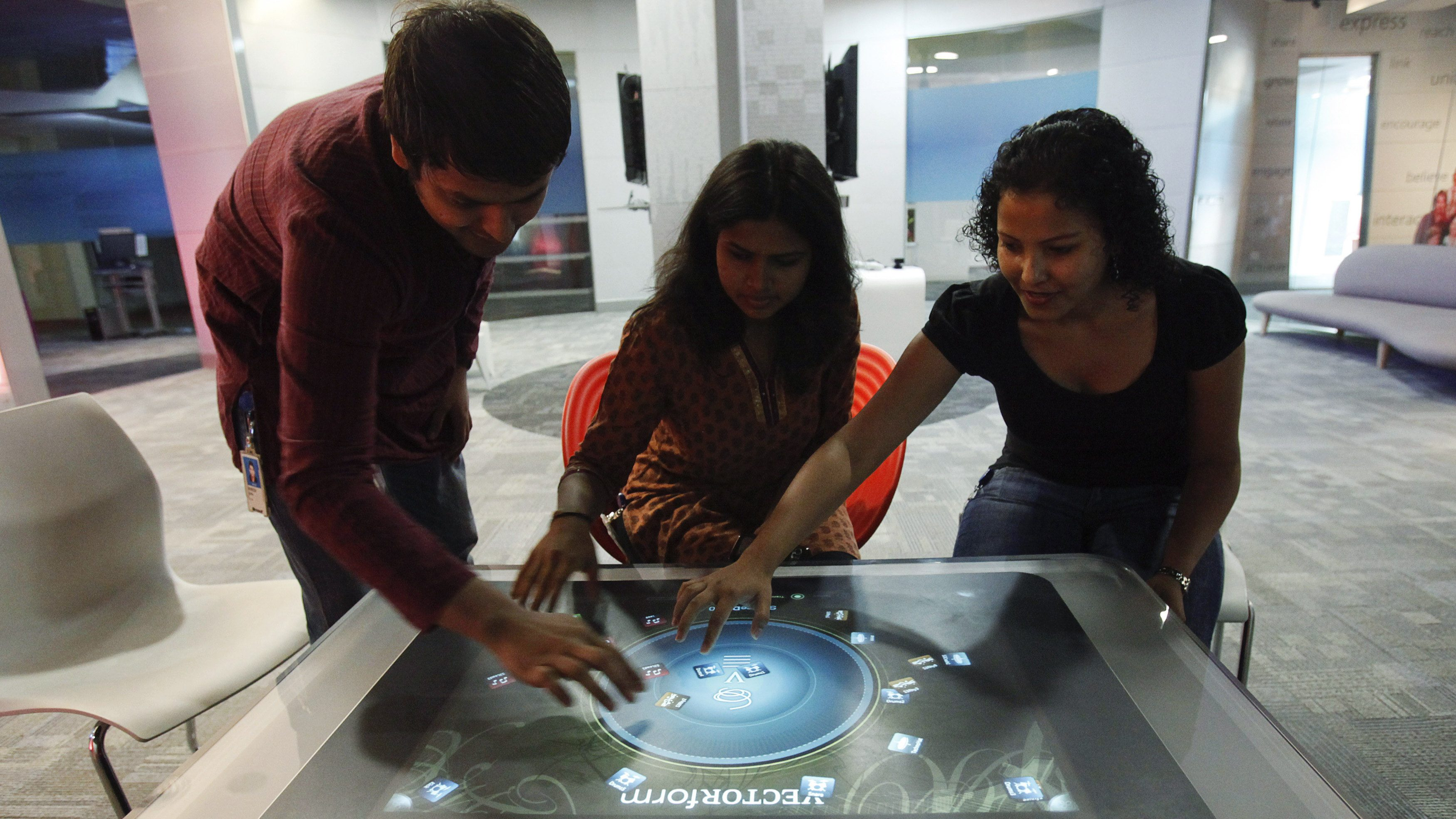 Employees demonstrate the use of the newly-designed prototype of a touch-sensitive table at Microsoft India's Development Center in the Gachibowli IT district in Hyderabad