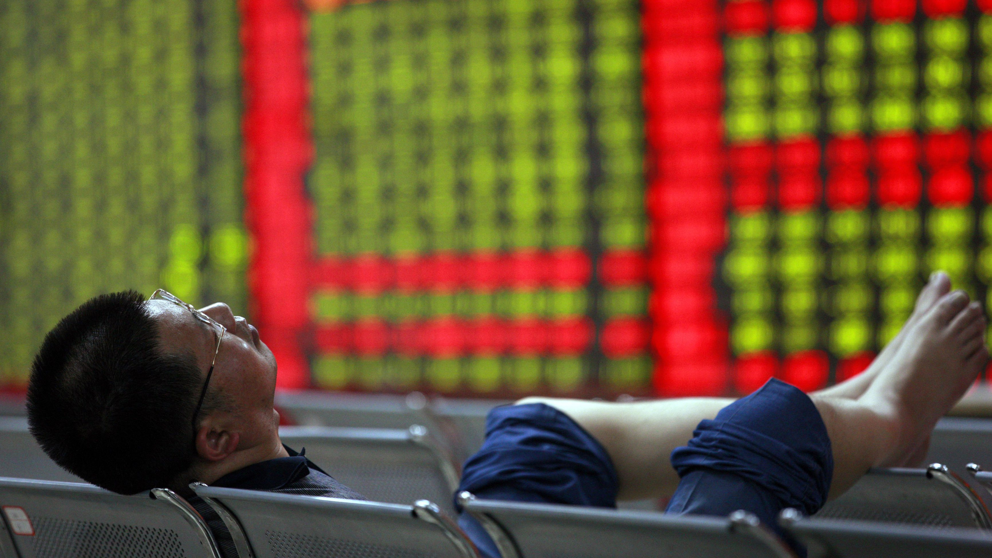An investor sleeps on a bench in front of an electronic board showing stock information at a brokerage house in Huaibei, Anhui province May 9, 2012. China shares produced its worst loss in six weeks on Wednesday, hit by weakness in growth-sensitive sectors on jitters that a possible delay to the start of the country's five-yearly congress could complicate economic recovery. The green figures on screen indicate falling prices.