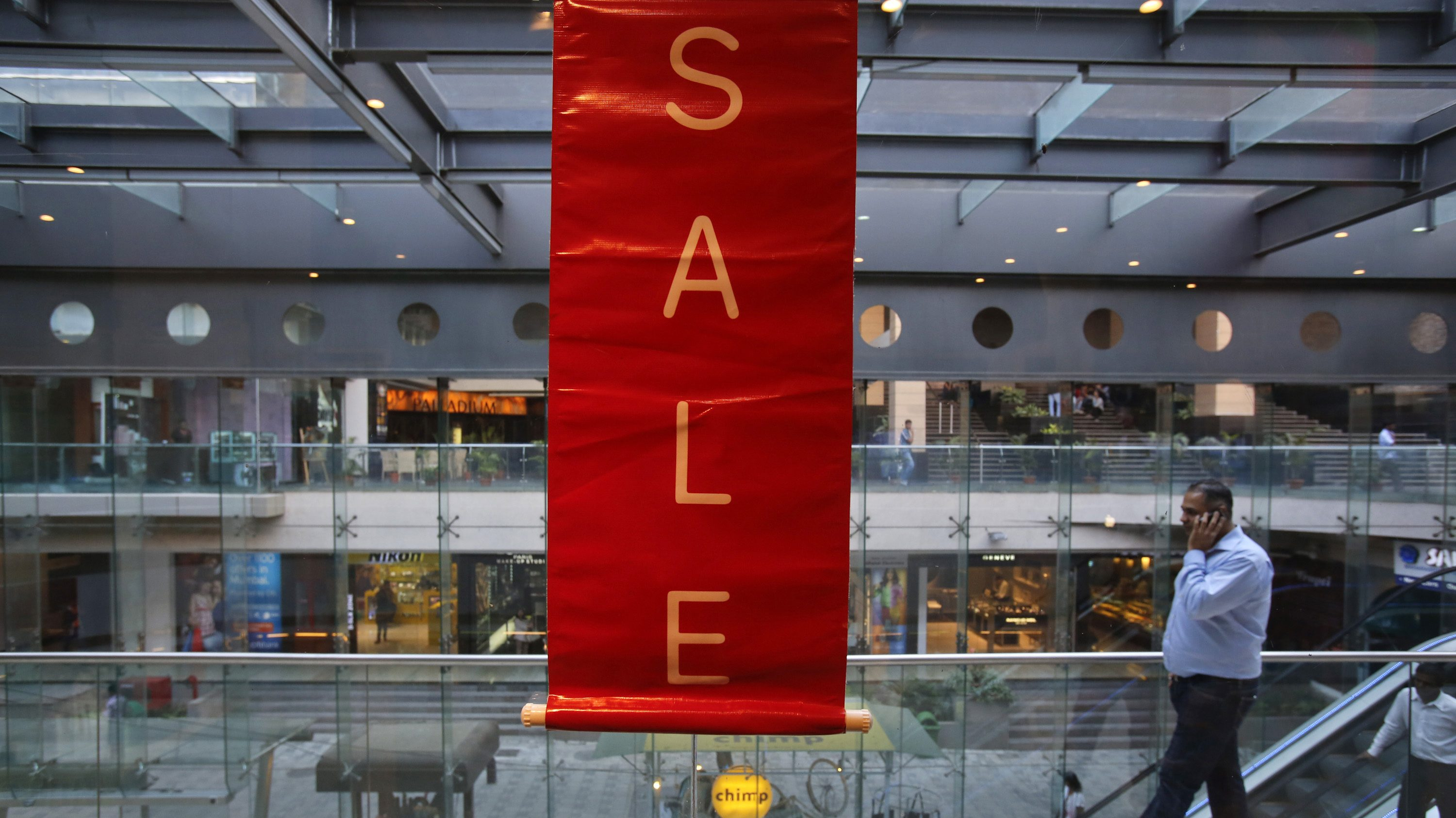A man walks past a sale poster in a shopping mall in Mumbai