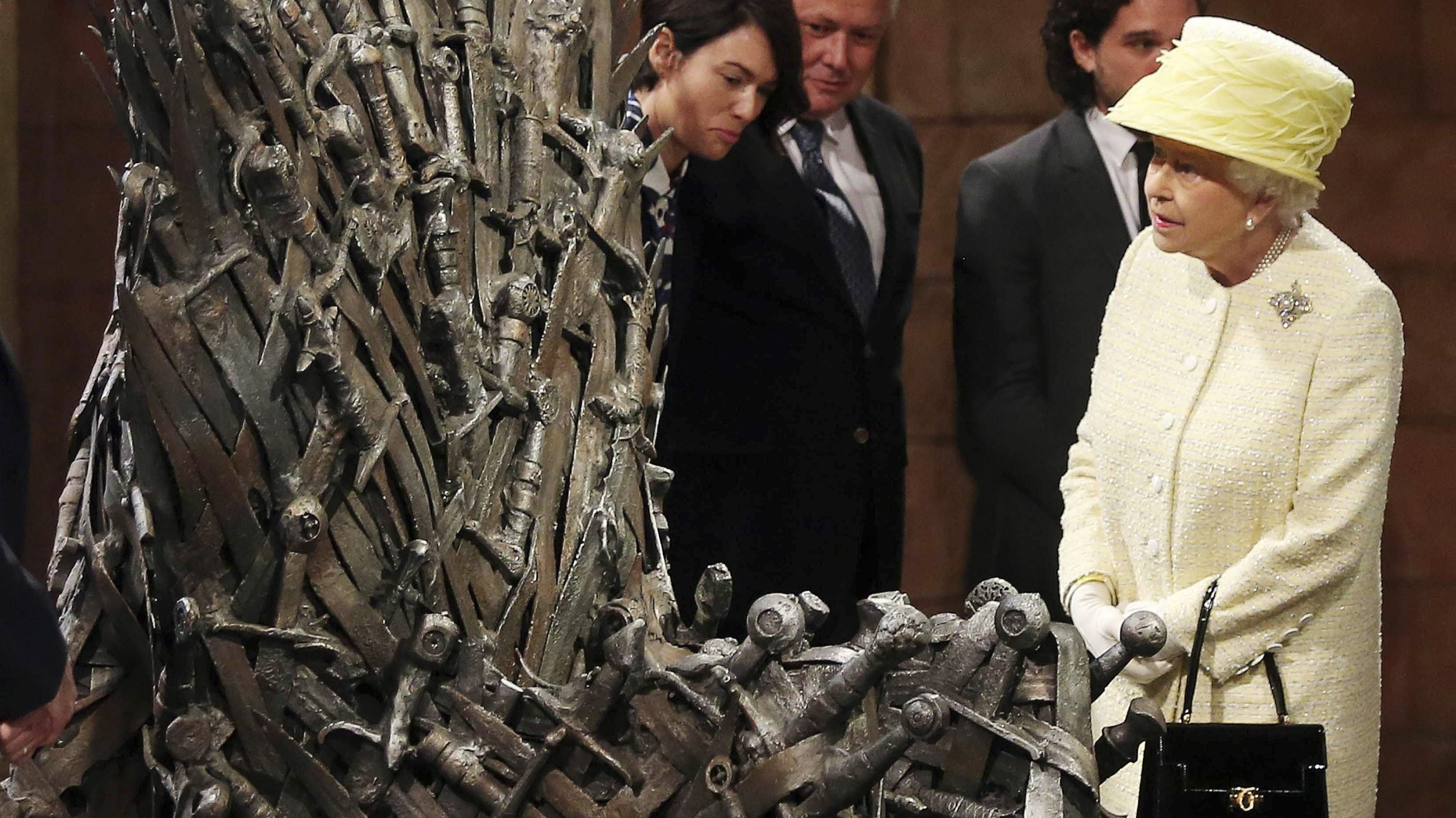 Britain's Queen Elizabeth looks at the Iron Throne next to Game of Thrones cast members Kit Harington (2nd R), Conleth Hill (2nd L) and Lena Headey (L), on the set of the television series in the Titanic Quarter of Belfast, Northern Ireland, June 24, 2014.