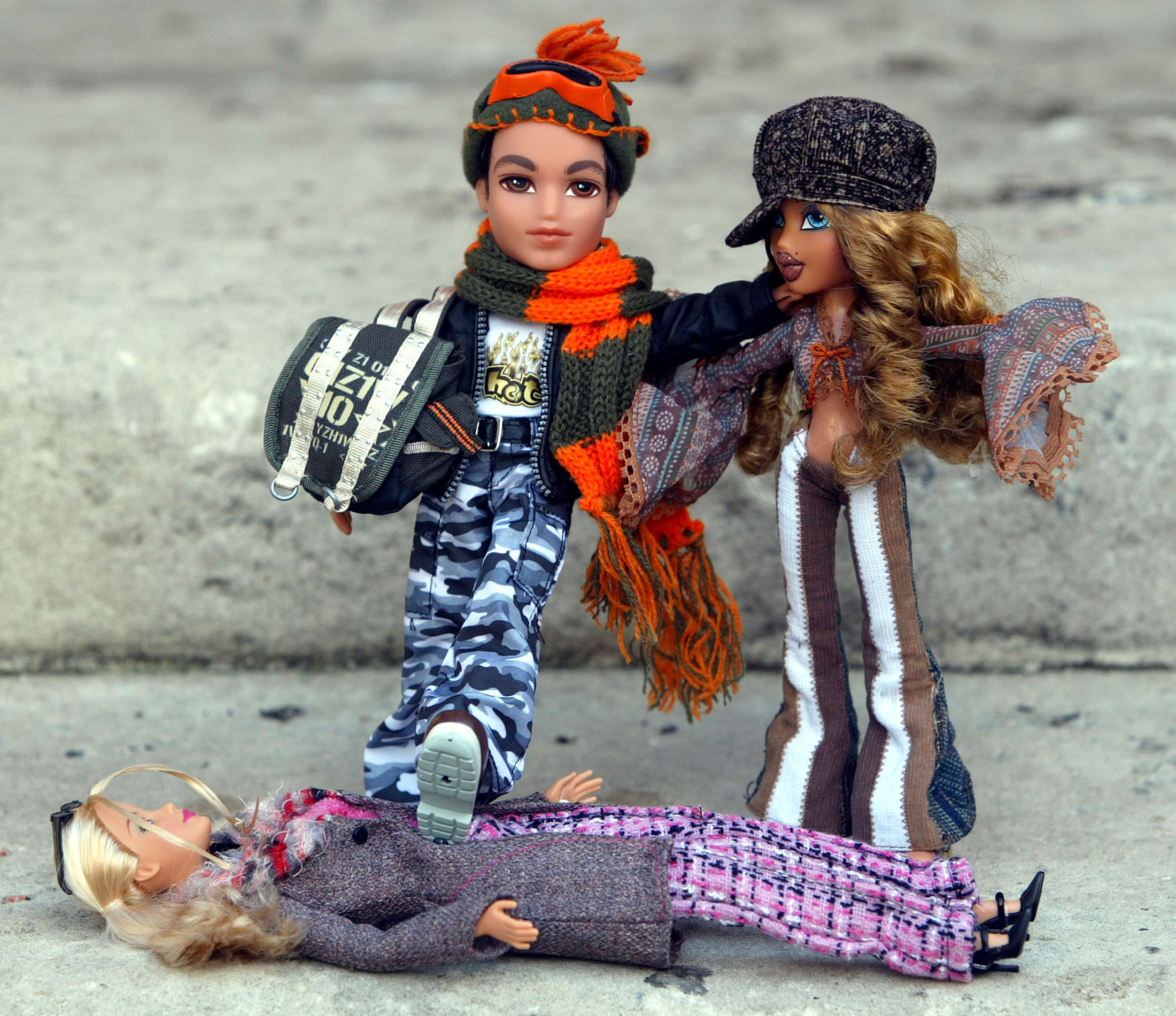 A Bratz doll (L) is seen with its foot on a Barbie Doll (lying down) and another Bratz doll (R) at the Dream Toys 2004 exhibition, which previews the year's top 10 toys and offers predictions from the Toy Retailers Association of the most popular toys for Christmas, in London, October 6, 2004. At the ripe old age of 45, Barbie was knocked off her perch on Wednesday by streetwise upstart Bratz in the Christmas battle of the dolls. REUTERS/Stephen Hird  SH/ASA/acm - RP5DRIEJWTAA