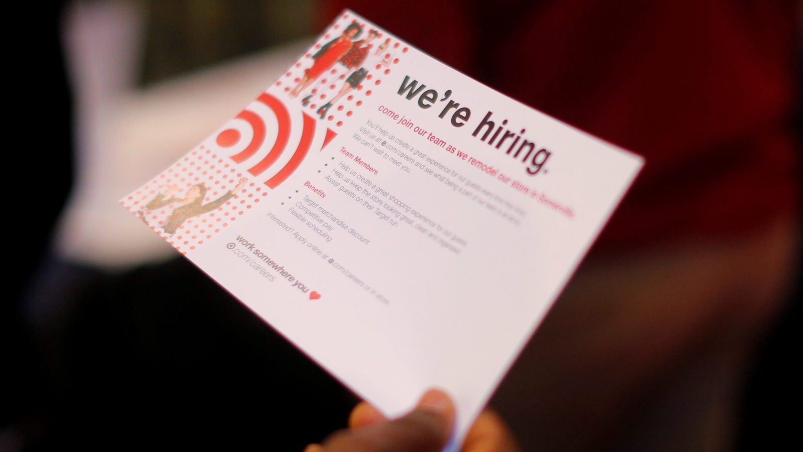"""A job seeker holds a """"We're Hiring"""" card while talking to a representative from Target at a City of Boston Neighborhood Career Fair on May Day in Boston, Massachusetts, U.S., May 1, 2017.   REUTERS/Brian Snyder - RC114BD2E780"""
