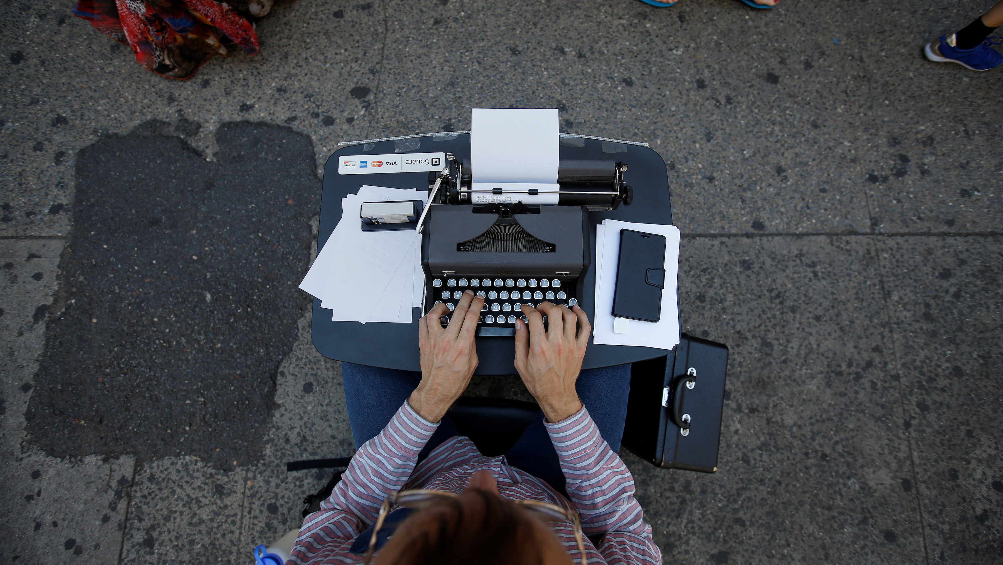 Street poet Allan Andre, who writes impromptu poems on an old typewriter, works on a composition on the sidewalk in New York City, New York, U.S., August 1, 2017. REUTERS/Carlo Allegri - RC1AC8AC9AD0