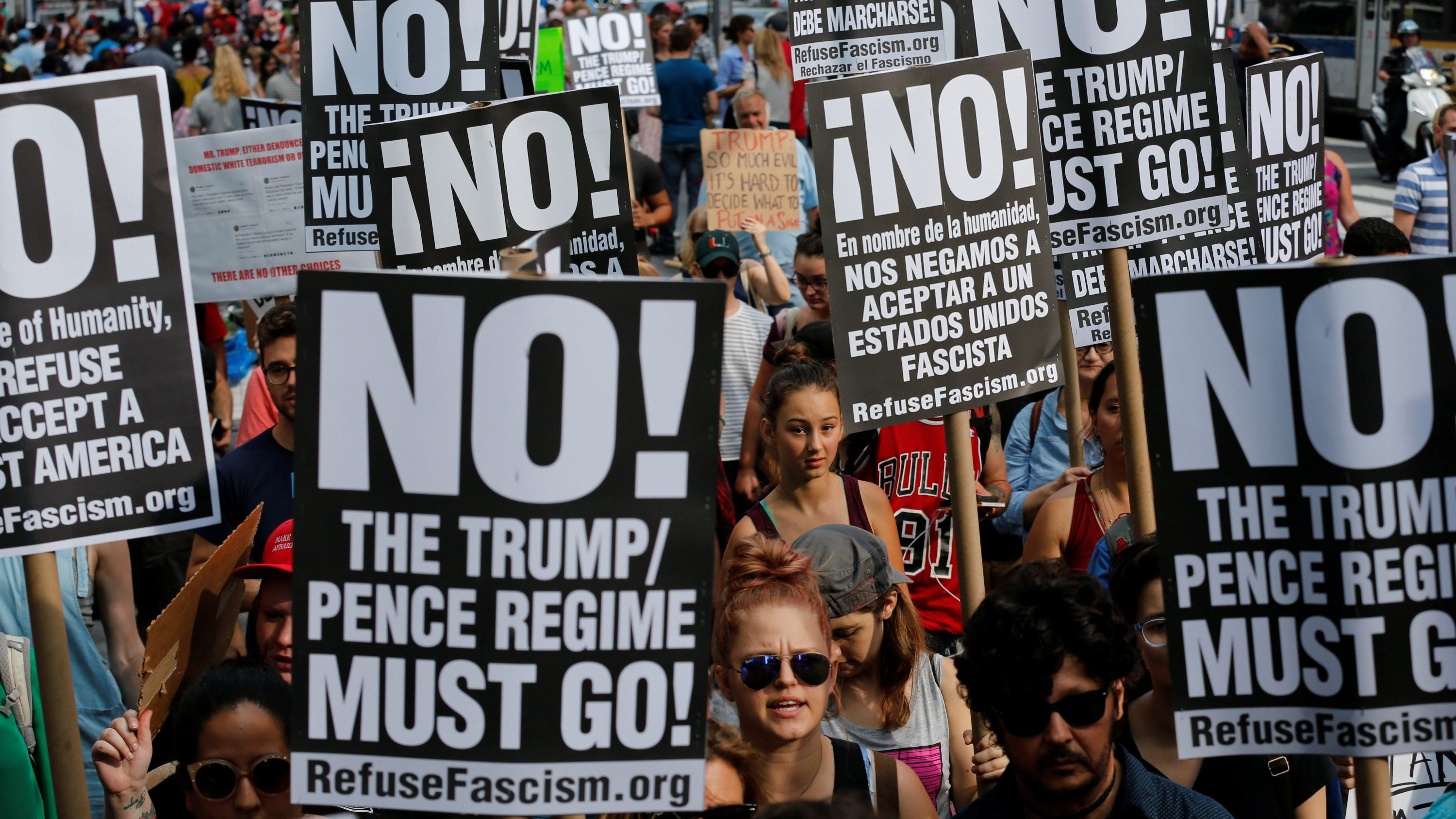 "Protesters hold signs reading ""No! The Trump/Pence regime must go!"" during a march against white nationalism in New York City, U.S., August 13, 2017."