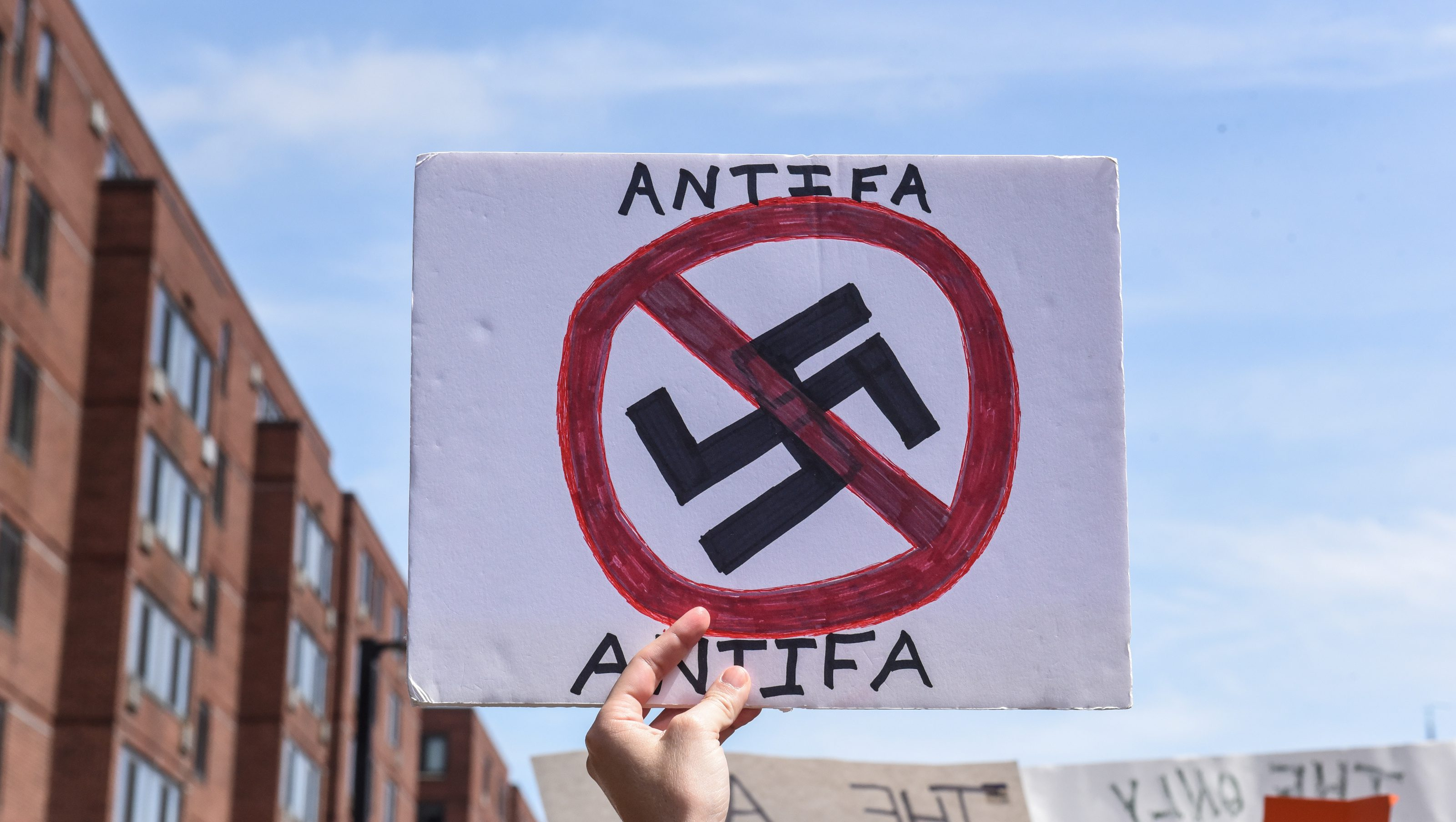 """A counter protester holds a sign with the words """"Antifa"""" (anti-fascists) outside of the Boston Commons and the Boston Free Speech Rally in Boston, Massachusetts"""