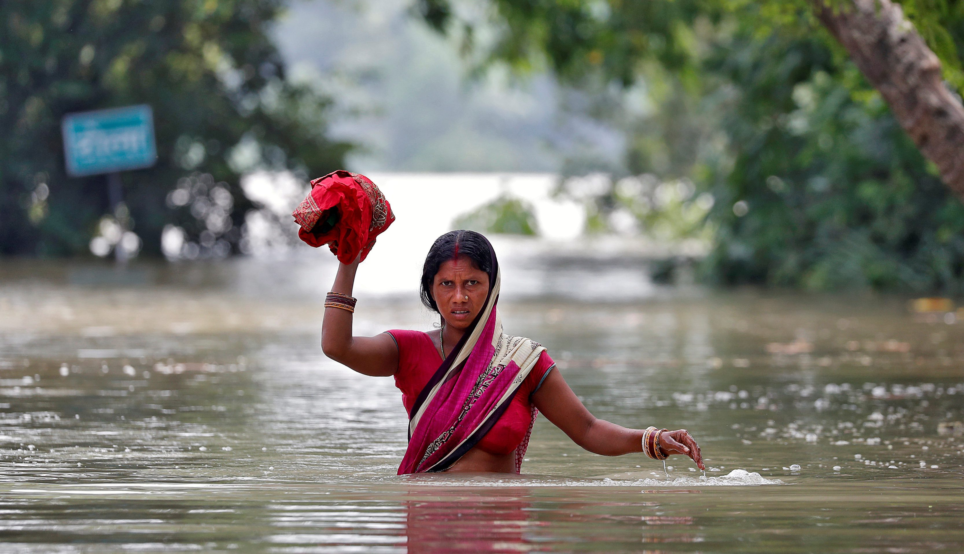 A woman wades through a flooded village in the eastern state of Bihar, India.