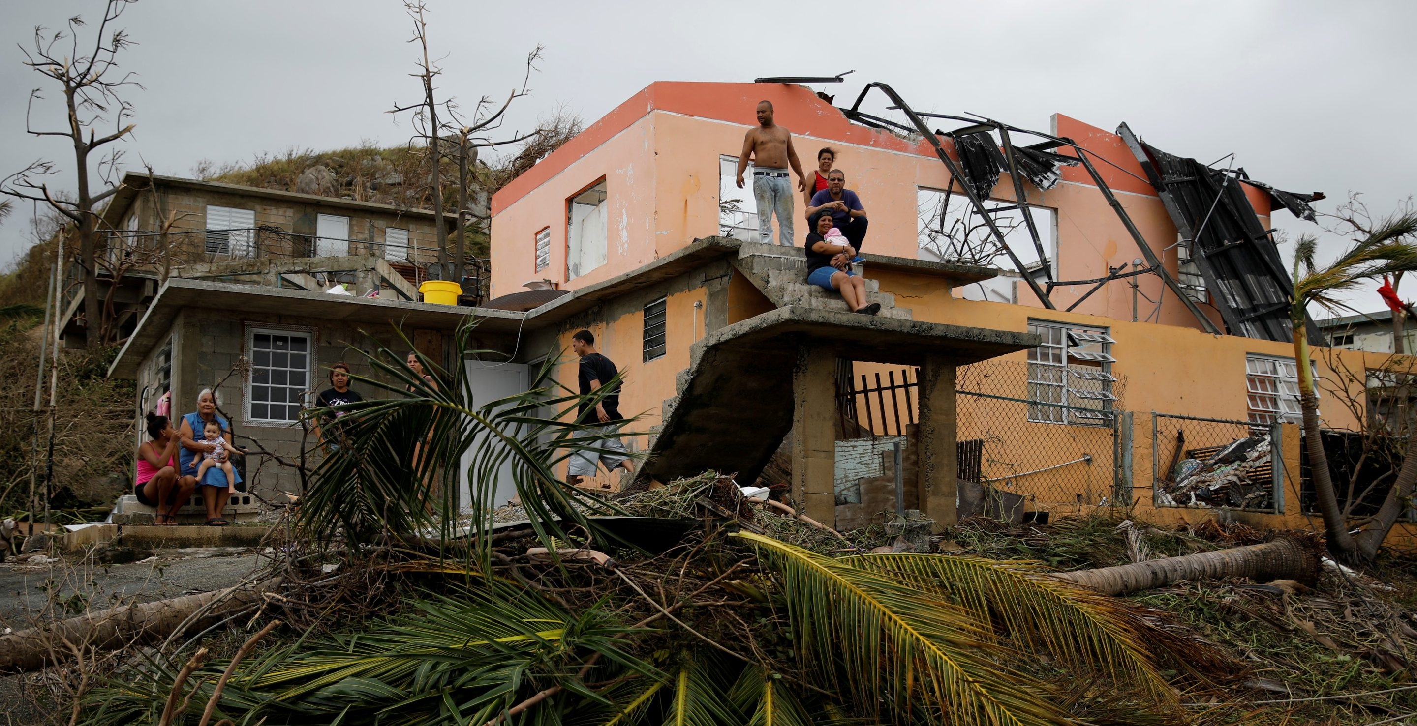 People rest outside a damaged house after the area was hit by Hurricane Maria in Yabucoa, Puerto Rico September 22, 2017. REUTERS/Carlos Garcia Rawlins     TPX IMAGES OF THE DAY - RC14BDD5D400