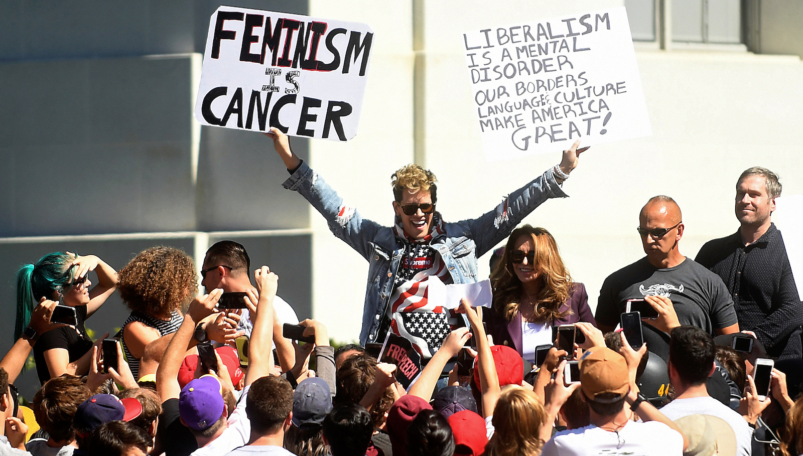 Conservative commentator Milo Yiannopoulos holds protest signs while speaking at the University of California in Berkeley, California, U.S., September 24, 2017. REUTERS/Noah Berger - RC1C6BA75150