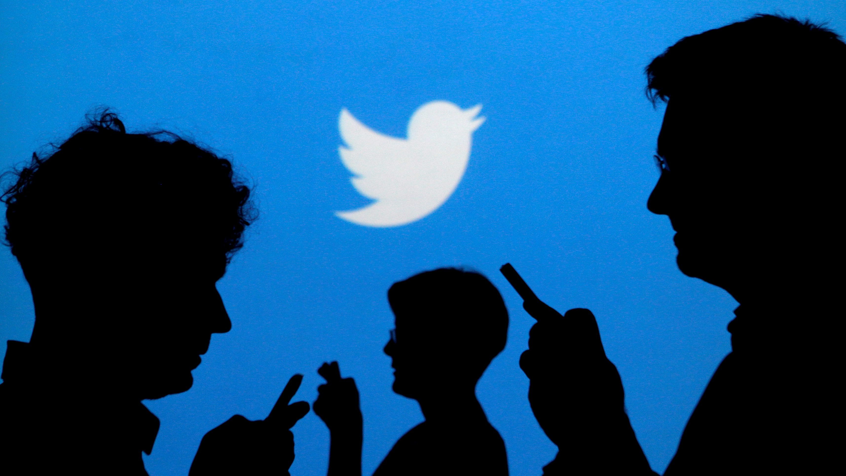FILE PHOTO: People holding mobile phones are silhouetted against a backdrop projected with the Twitter logo in this illustration picture taken September 27, 2013. REUTERS/Kacper Pempel/Illustration/File Photo - RC14CA681FC0