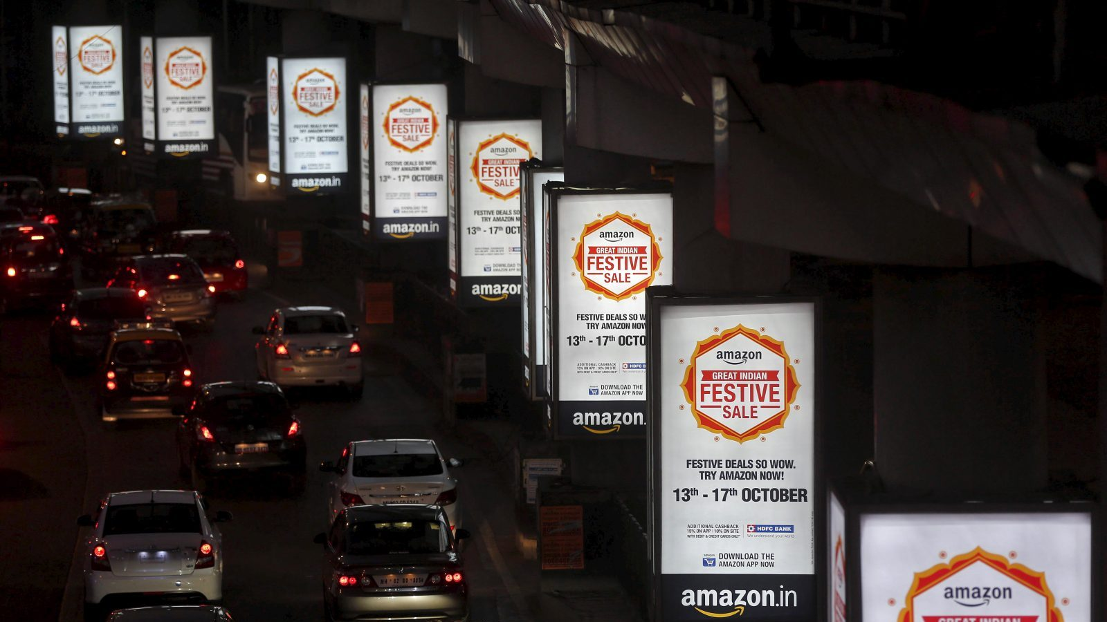Traffic moves on a road past advertisements of Indian online marketplace Amazon, in Mumbai, India, October 15, 2015. Amazon.com could emerge as the biggest winner from one of India's most important festive - and shopping - seasons that began this week, after the e-tailer offered steep discounts, swift delivery and even gold bars to grab market share. The month-long festive season culminates around November 10 in Diwali, or the Festival of Lights, but the first nine days are considered an especially auspicious time to make big purchases. Picture taken October 15, 2015.   REUTERS/Shailesh Andrade - GF10000246868