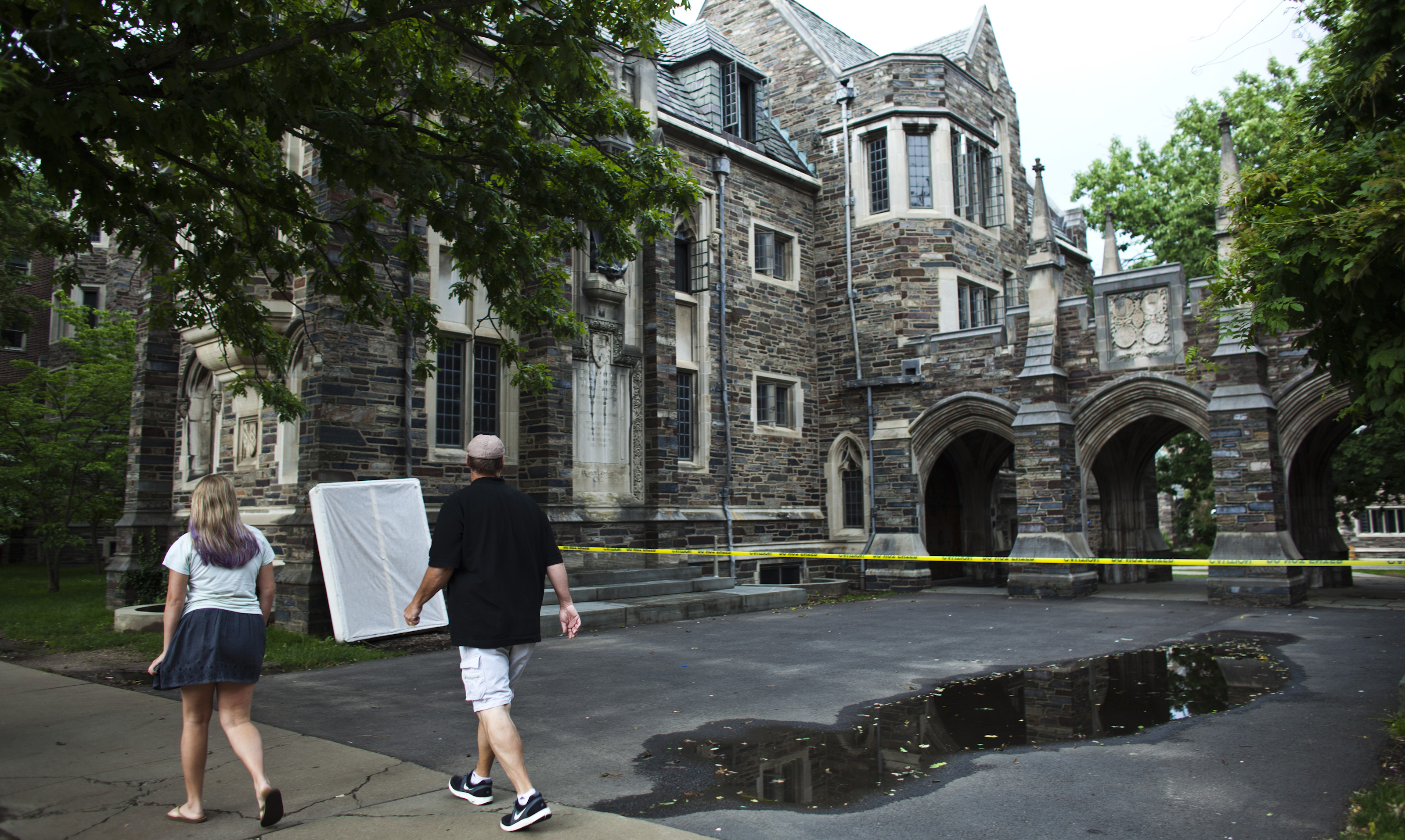 People walk pass a caution tape at one of the entrance of Princeton University in New Jersey June 11, 2013. Princeton University evacuated its sprawling campus in New Jersey on Tuesday after receiving a bomb threat to multiple buildings, the latest of threats that have disrupted schools, government buildings and air travel across the country the past two days. REUTERS/Eduardo Munoz (UNITED STATES - Tags: CRIME LAW EDUCATION) - GM1E96C0AIA01