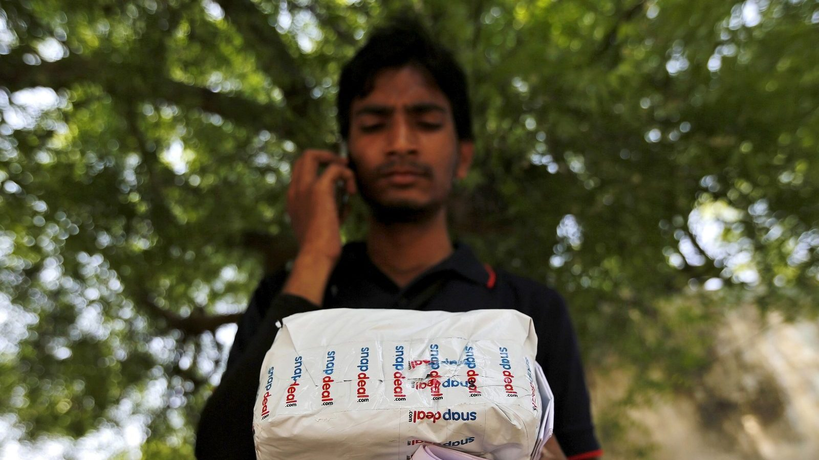 A worker of Indian e-commerce company Snapdeal.com makes a call to a customer before delivering a packet in Ahmedabad, India, April 17, 2015. After losing top engineering talent for years to America's tech heartland of Silicon Valley, India is luring them back as an e-commerce boom sparks a thriving start-up culture, unprecedented pay, and perks including free healthcare for in-laws. Picture taken April 17, 2015. To match INDIA-ECOMMERCE/WORKERS. REUTERS/Amit Dave  - GF10000082310