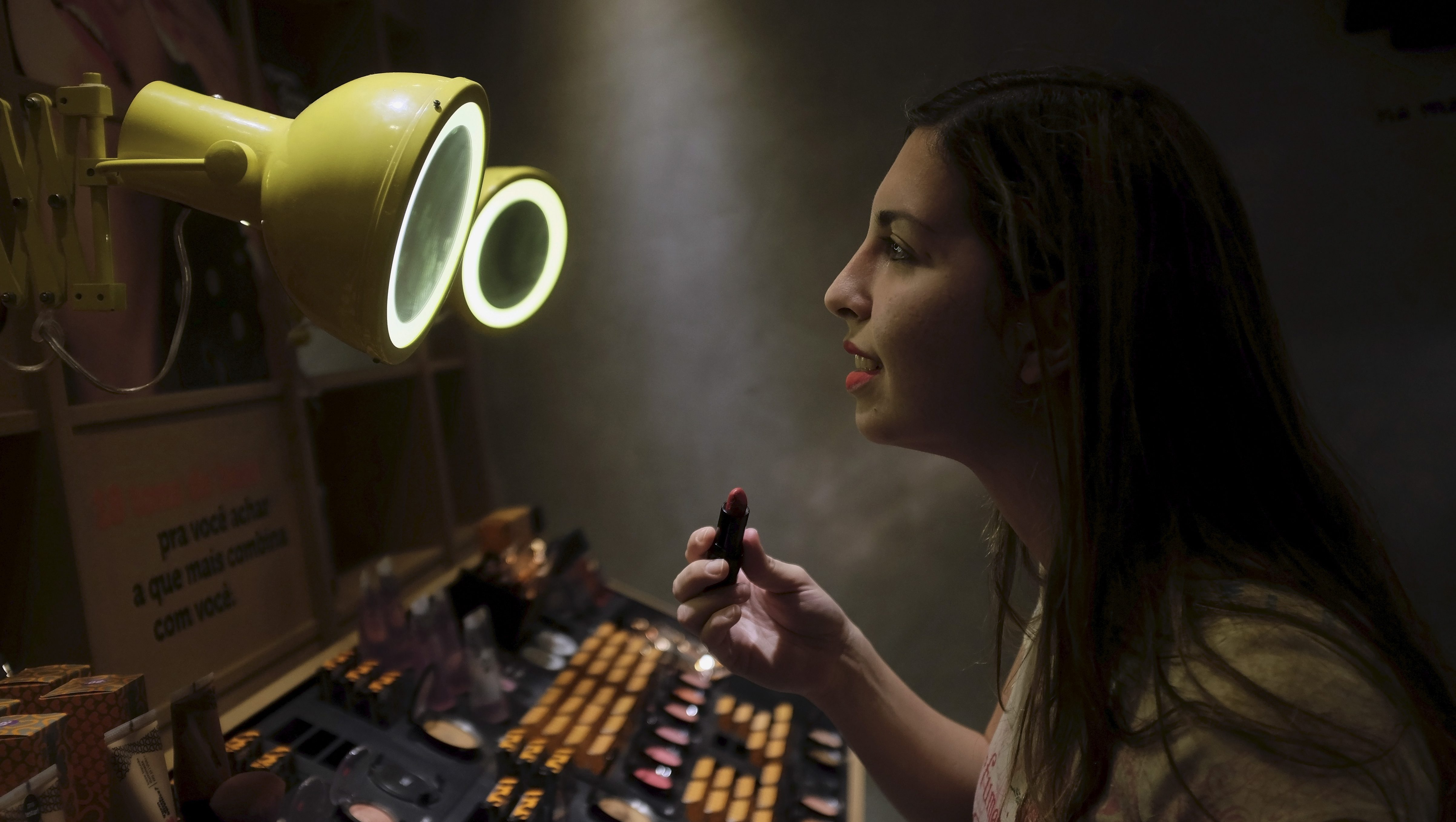 A woman checks lipstick applied on her lip, inside of a cosmetics shop in Sao Paulo, Brazil August 13, 2015. From cigarettes to lipstick to sandals, exports have emerged as a silver lining for Brazilian consumer goods companies that are suffering the worst domestic slump in over a decade. With Brazil's currency, the real, at a 12-year low, foreign sales have kept several companies in the black, helping them outperform rivals focused on the local market, according to a Reuters analysis of second-quarter earnings. REUTERS/Nacho Doce - GF10000173277
