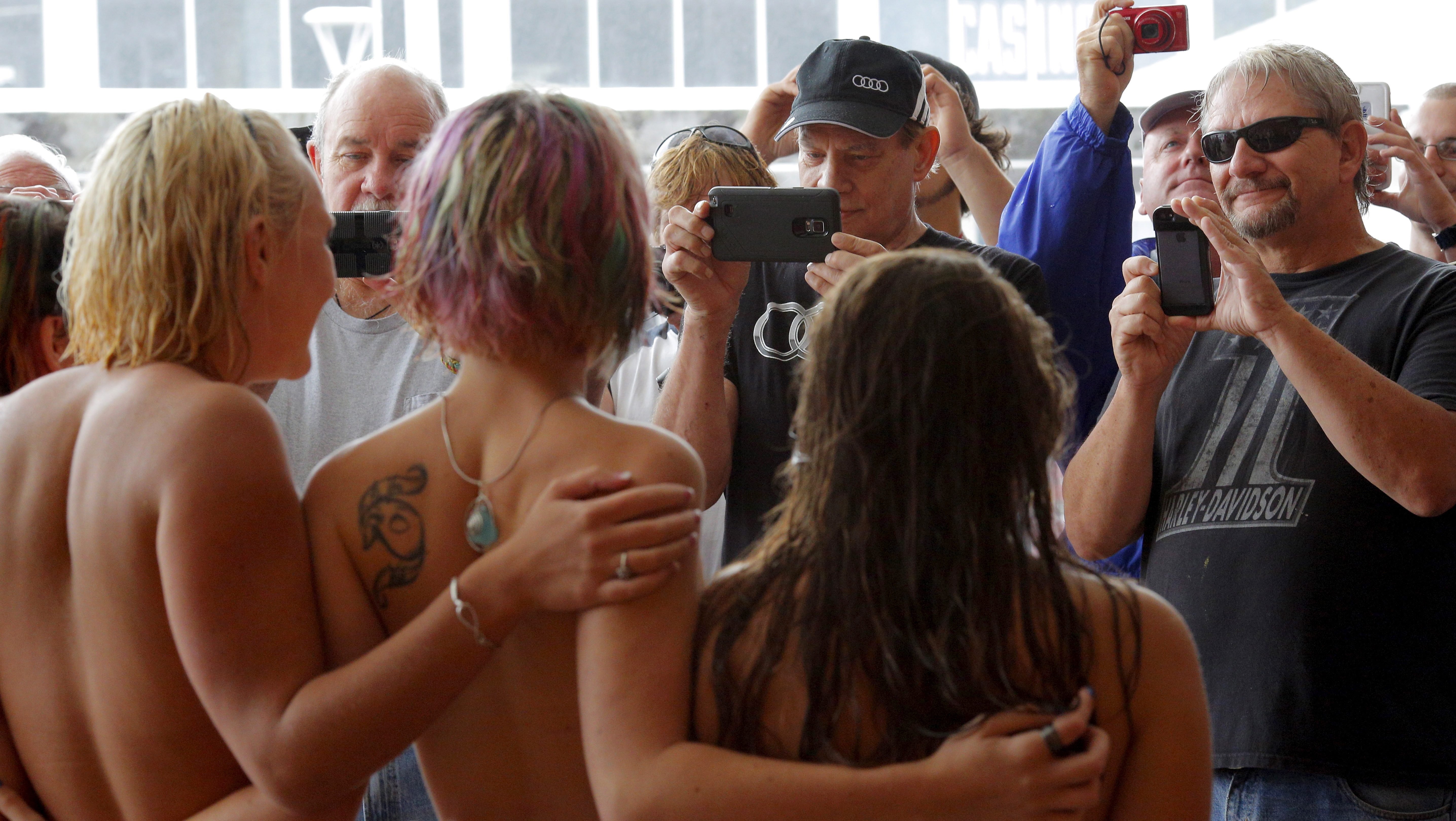 """Topless activists pose for photographs for onlookers during a """"Free the Nipple"""" demonstration in Hampton Beach, New Hampshire August 23, 2015. Hundreds of bare-breasted women are expected to converge on a popular New Hampshire beach on Sunday to push for greater acceptance of topless sunbathing, much to the consternation of some local residents and officials.   REUTERS/Brian Snyder - GF10000180542"""
