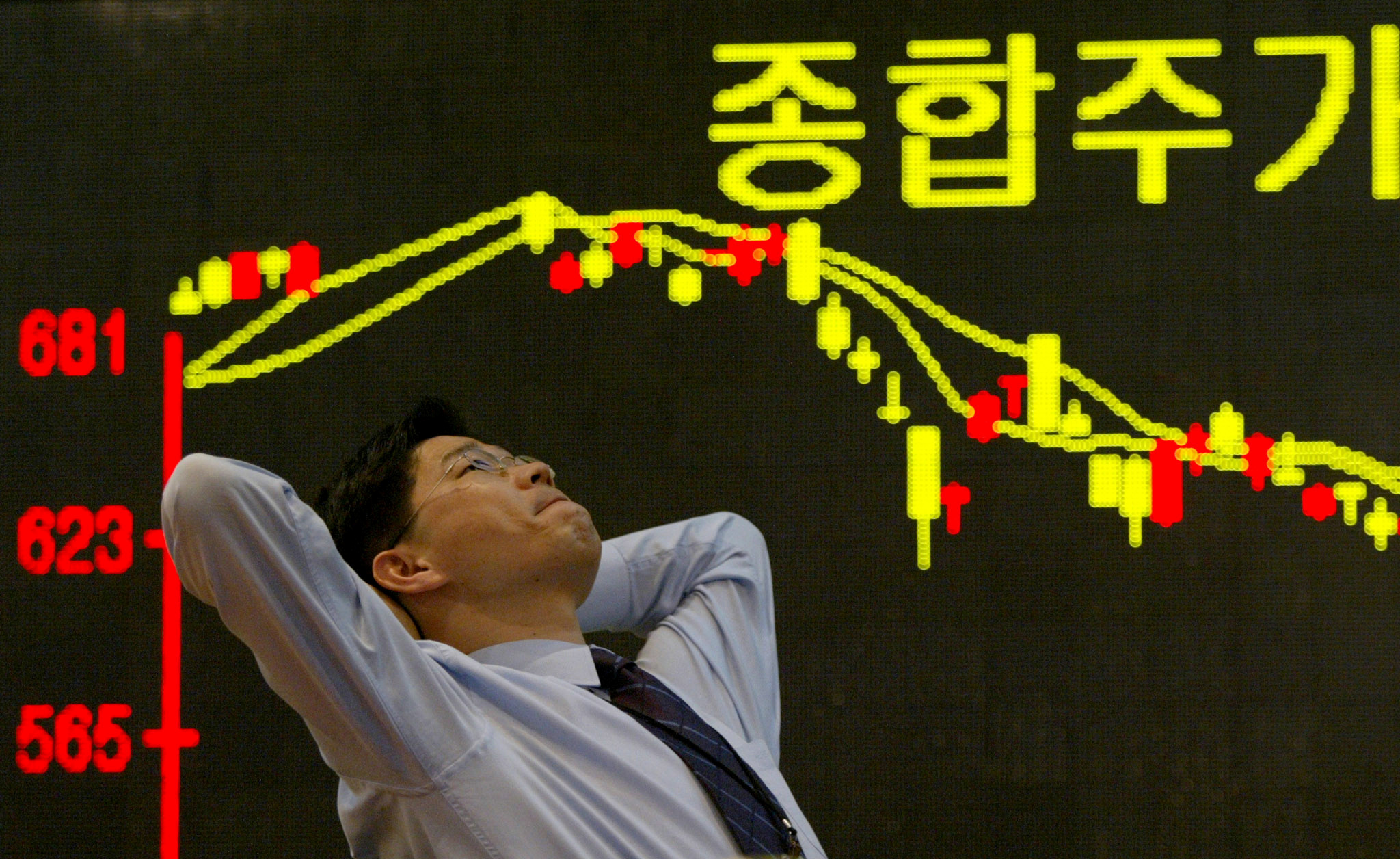 FILE PHOTO: A South Korean employee of a securities firm reacts in front of a graph showing stock price in Seoul March 11, 2003. /File photo - S1AETLECOXAA