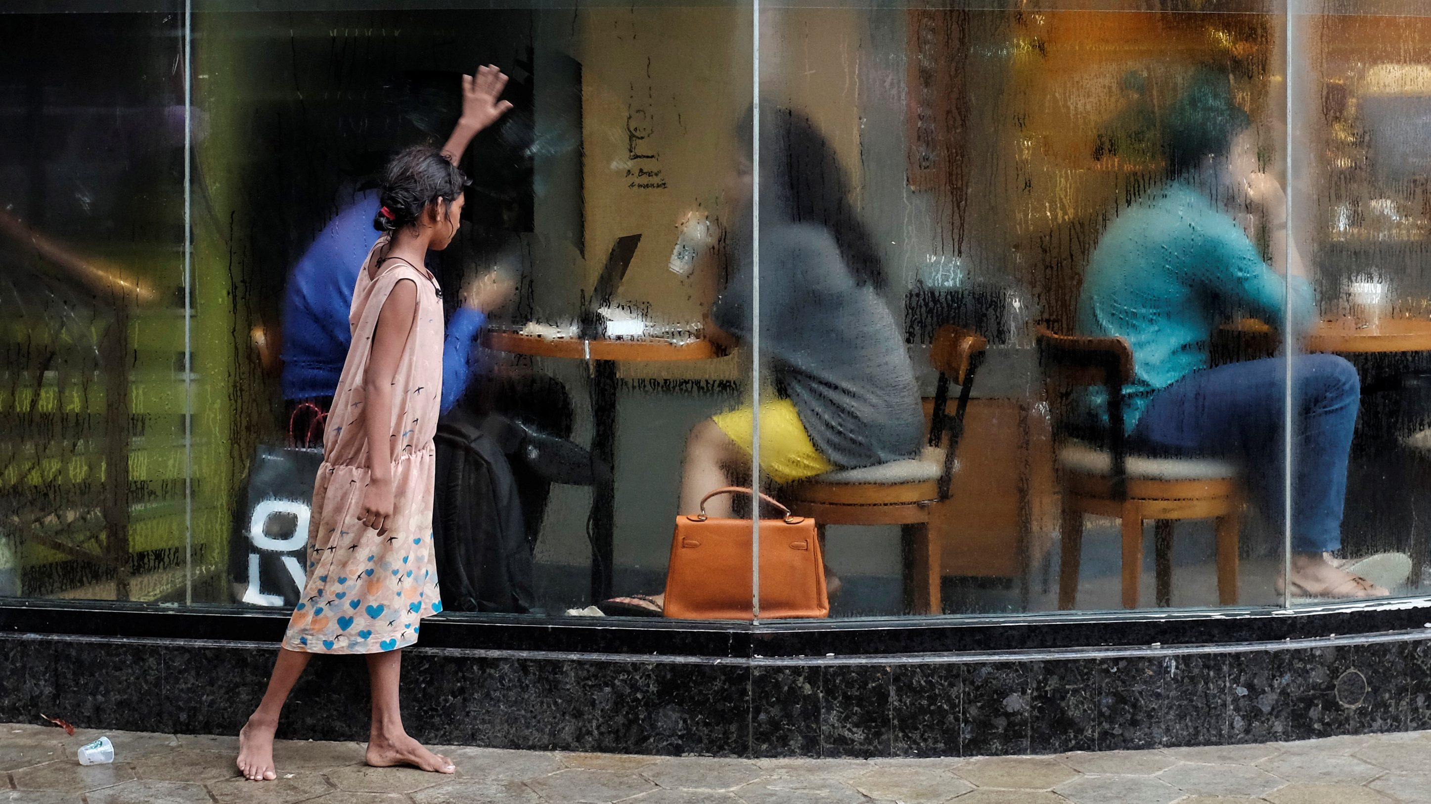 A homeless girl asks for alms outside a coffee shop in Mumbai