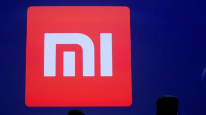 Attendants are silhouetted in front of Xiaomi's logo at a venue for the launch ceremony of Xiaomi's new smart phone Mi Max in Beijing, May 10, 2016.