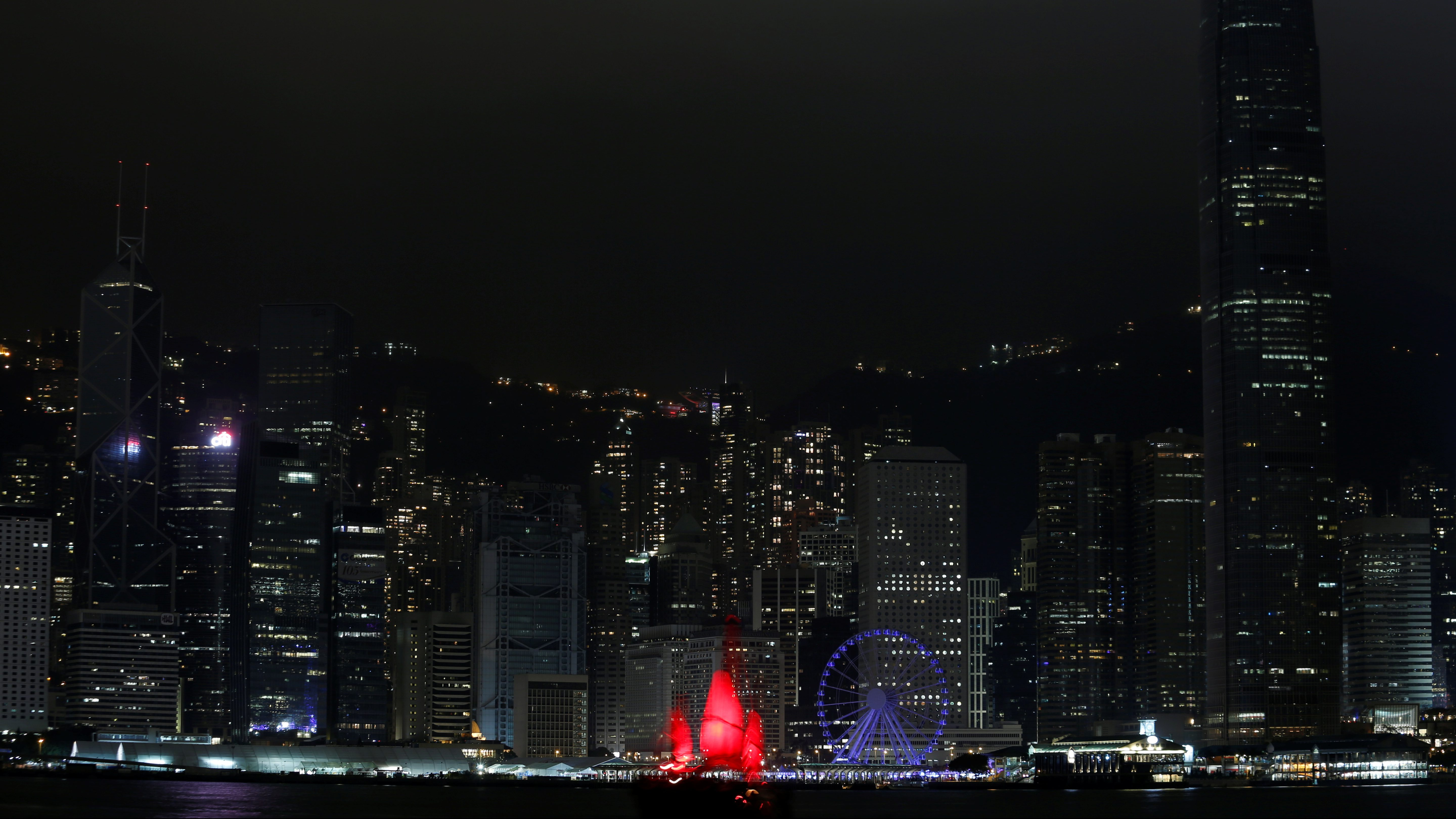 A tourist junk sails past as most of the lights in buildings in the financial Central District are switched off during Earth Hour in Hong Kong, China March 25, 2017.   - RC1D220AF890