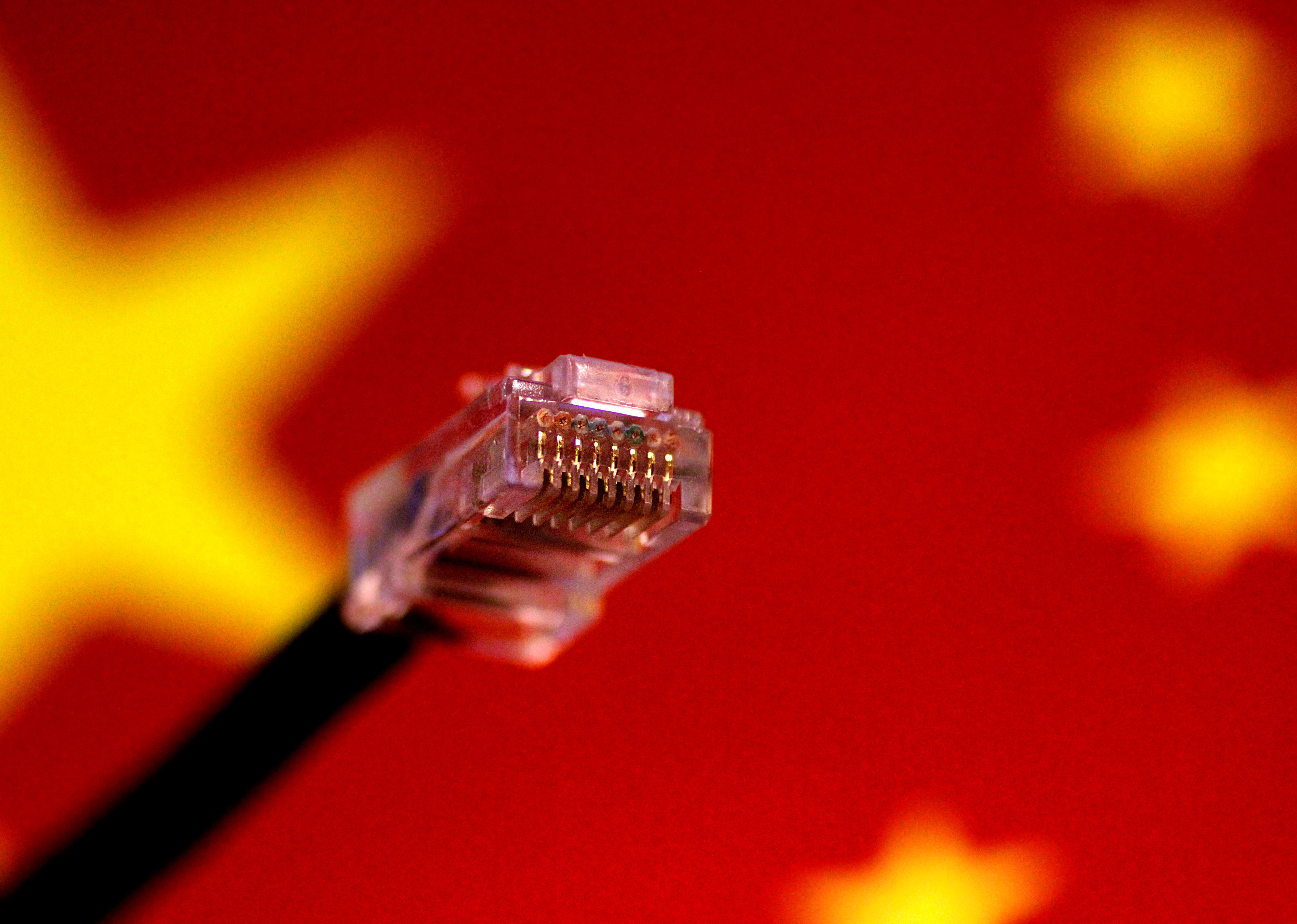 A computer network cable is seen above a Chinese flag in this July 12, 2017 illustration photo.   REUTERS/Thomas White/Illustration - RC174E6A26A0