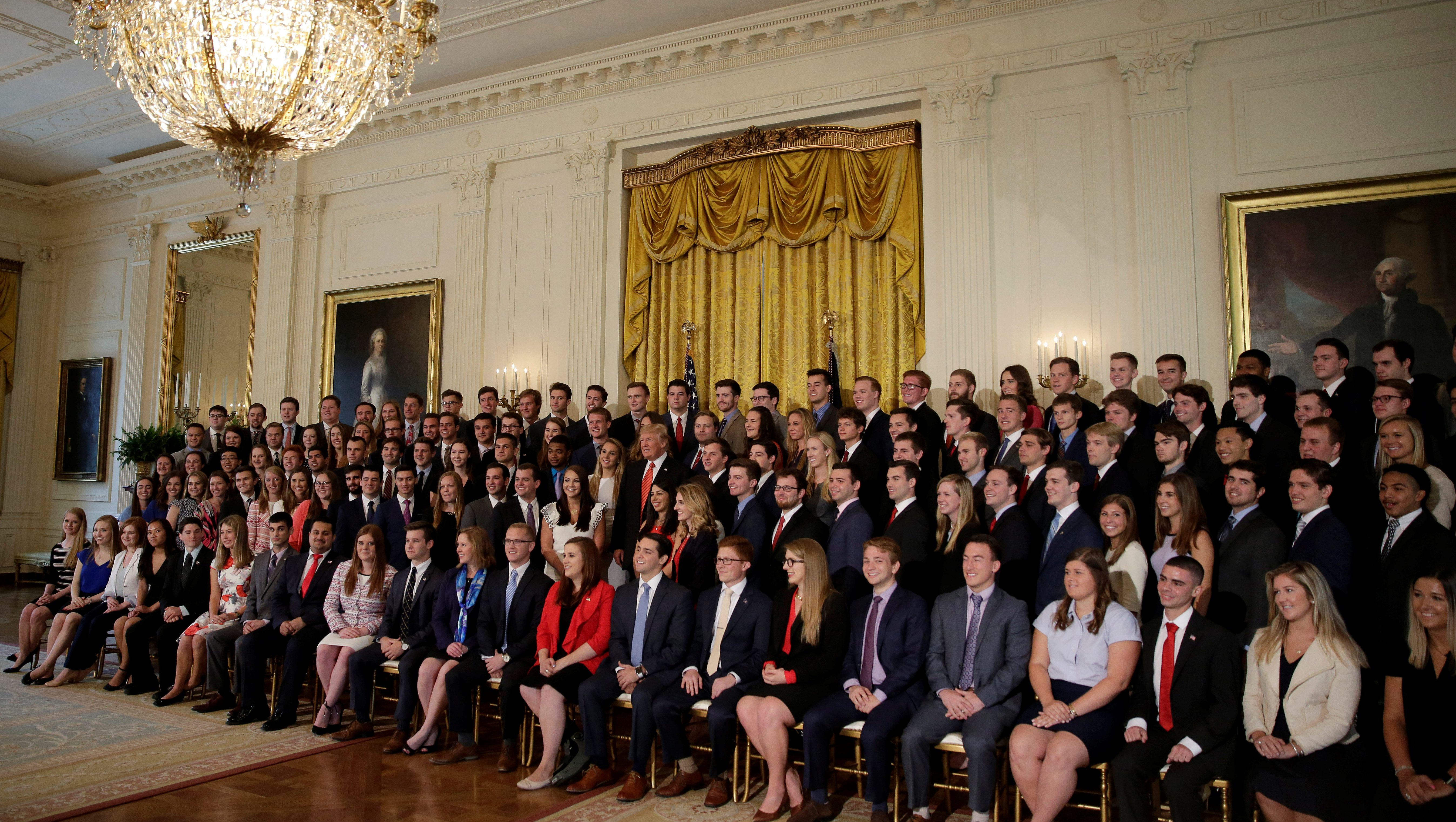 US President Donald Trump stands with departing White House interns as he poses for a photograph with them