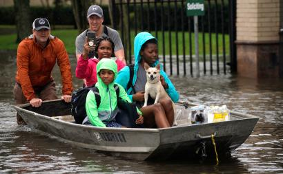 A family is evacuated by boat from the Hurricane Harvey floodwaters in Houston