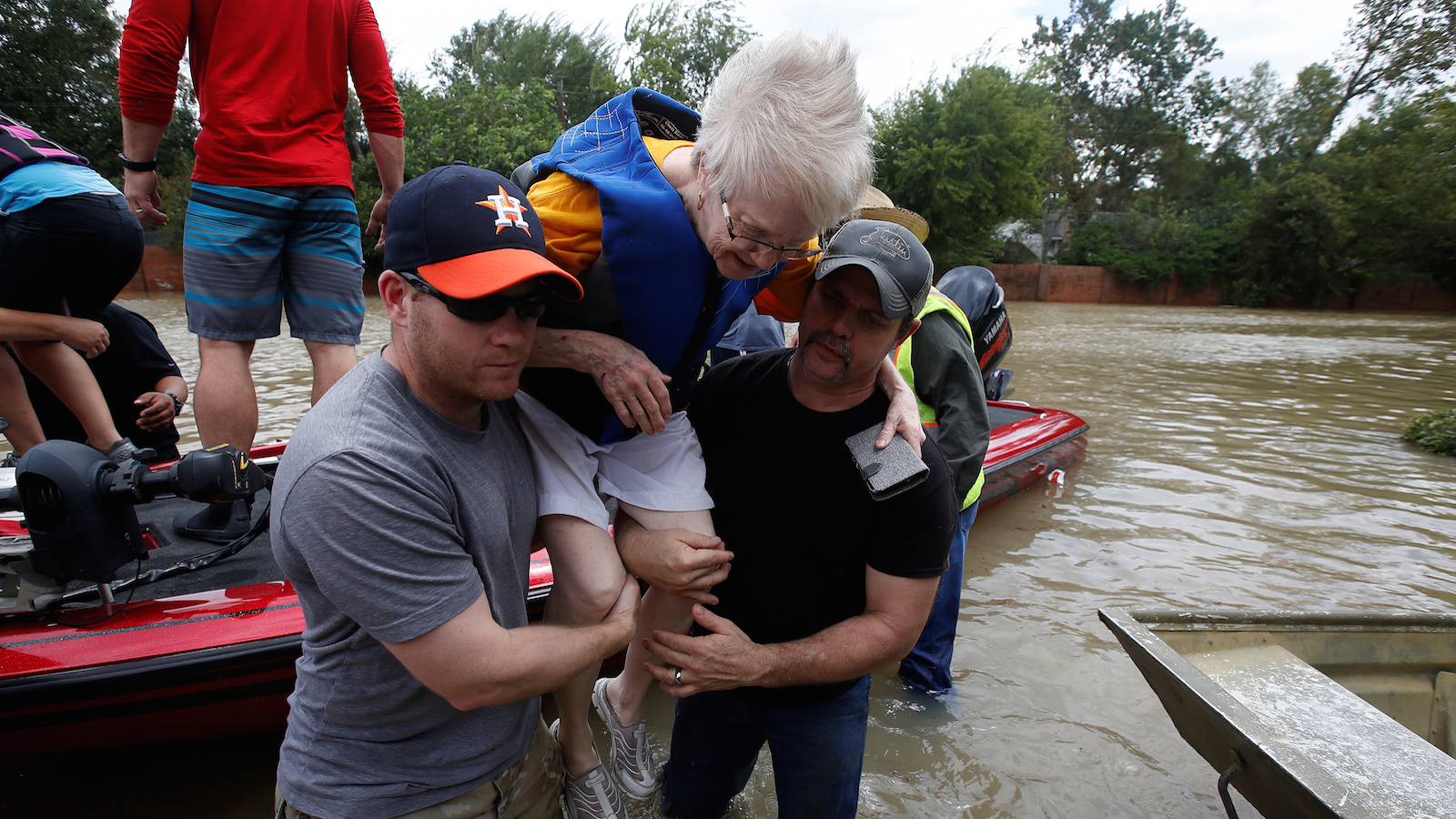Volunteers help a woman from a rescue boat as it evacuates people from the rising waters of Buffalo Bayou following Hurricane Harvey in a neighborhood west of Houston