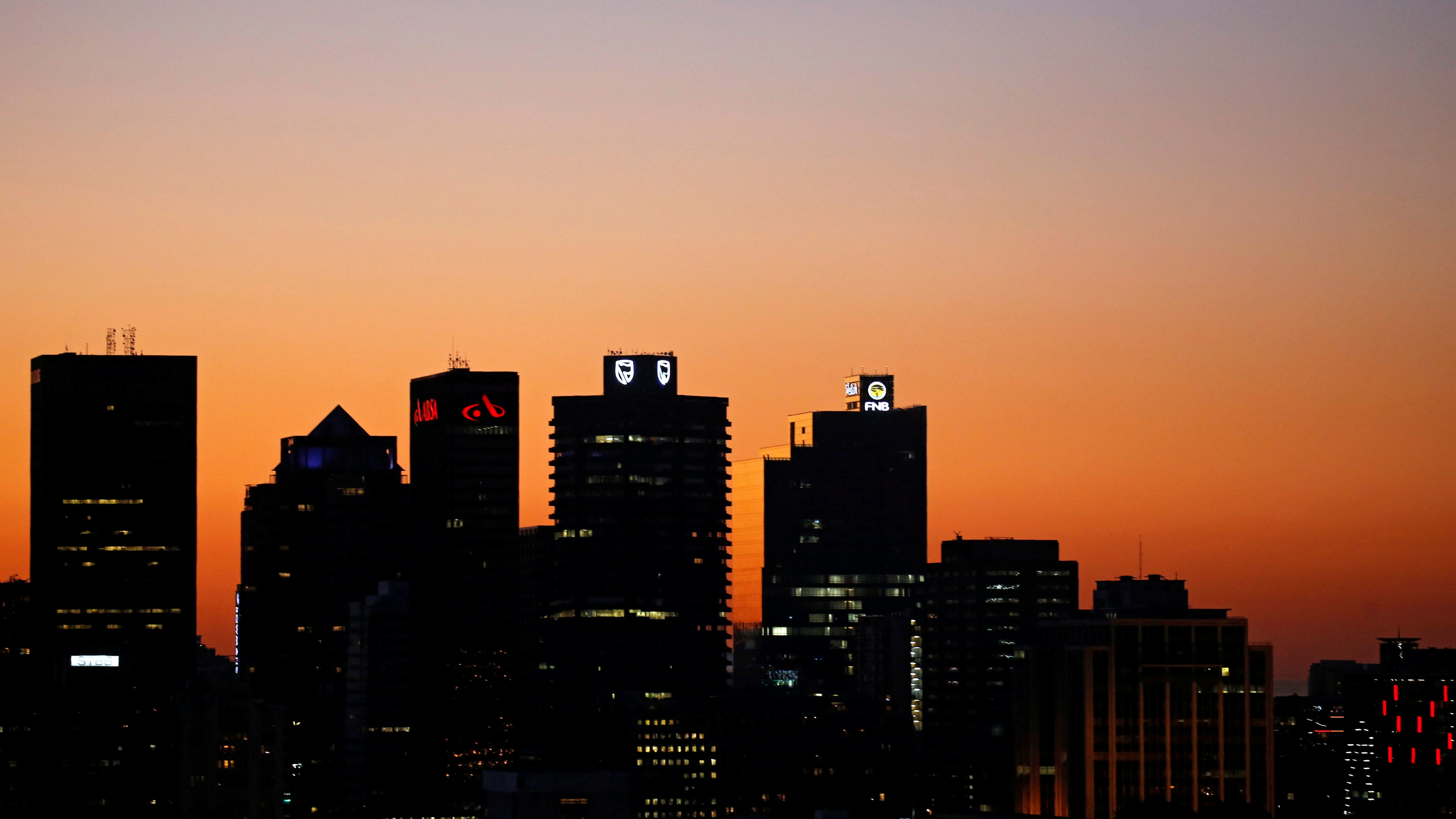 The buildings with the logos of three of South Africa's biggest banks, ABSA, Standard Bank and First National Bank are seen against the city skyline in Cape Town