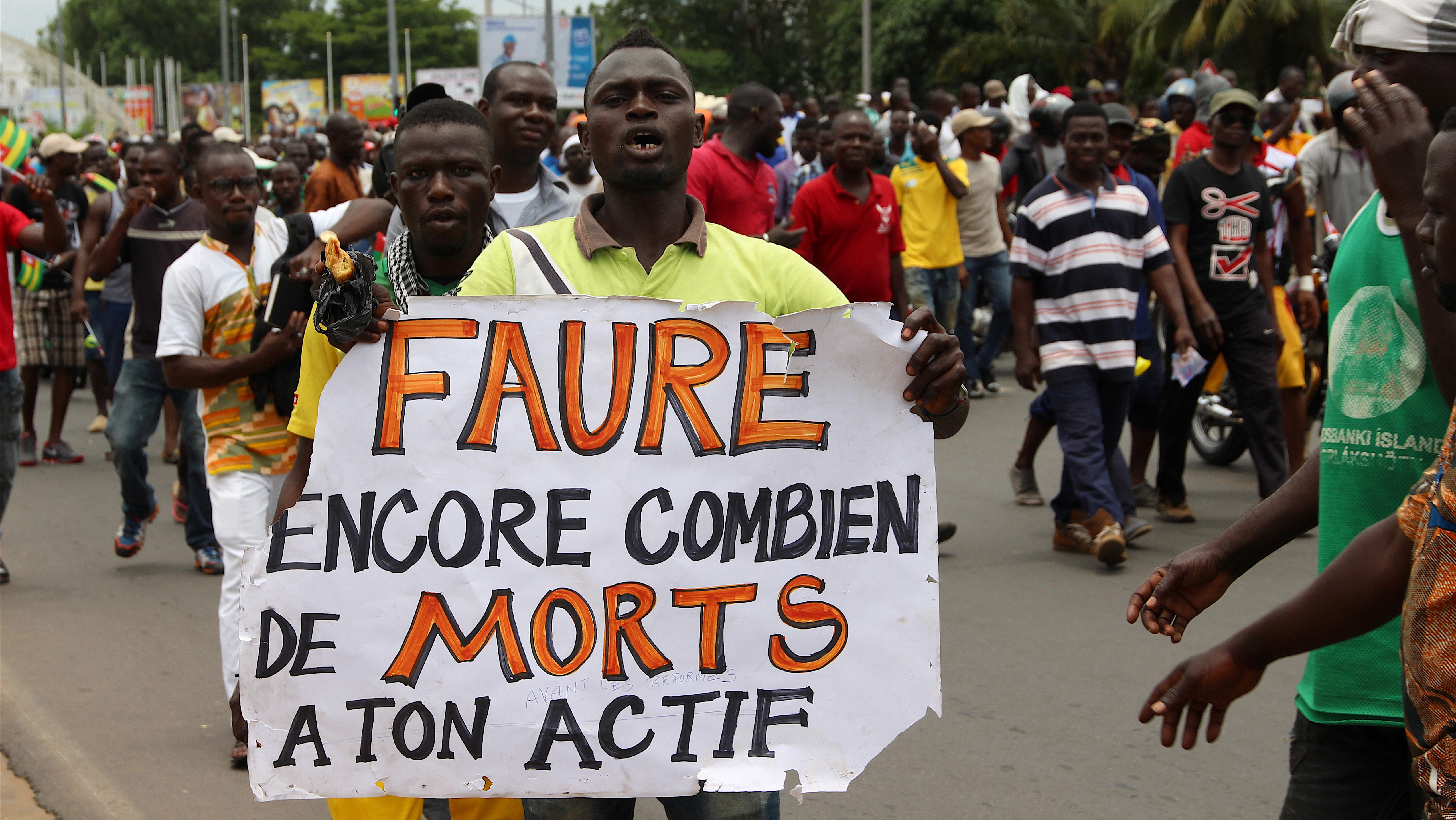 """A man holds up a sign, which reads: """"Faure still how many death by you"""", during an opposition protest calling for the immediate resignation of President Faure Gnassingbe in Lome, Togo, September 6, 2017."""
