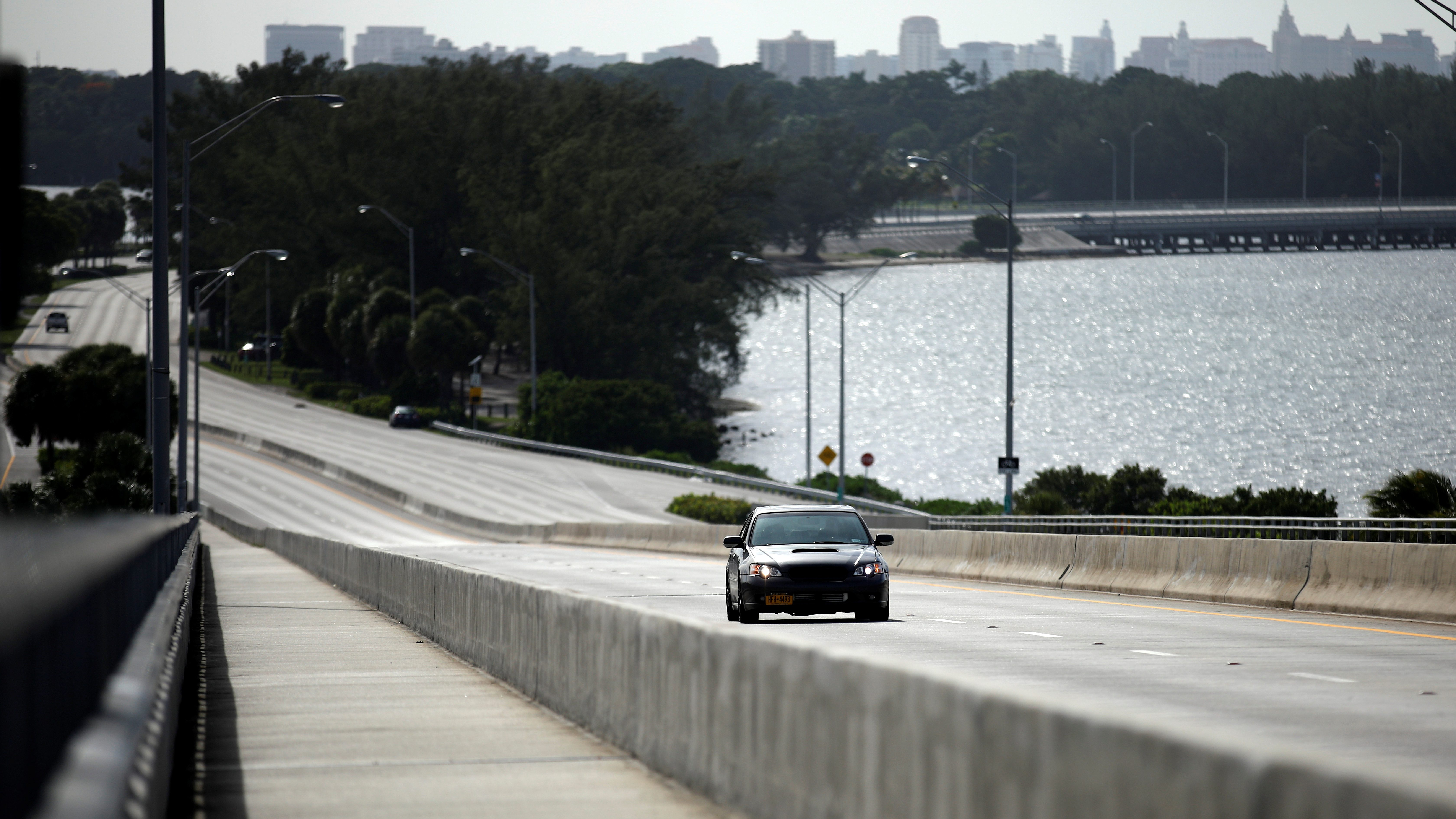 A car drives on an empty highway in downtown Miami before the arrival of Hurricane Irma to south Florida, in Miami