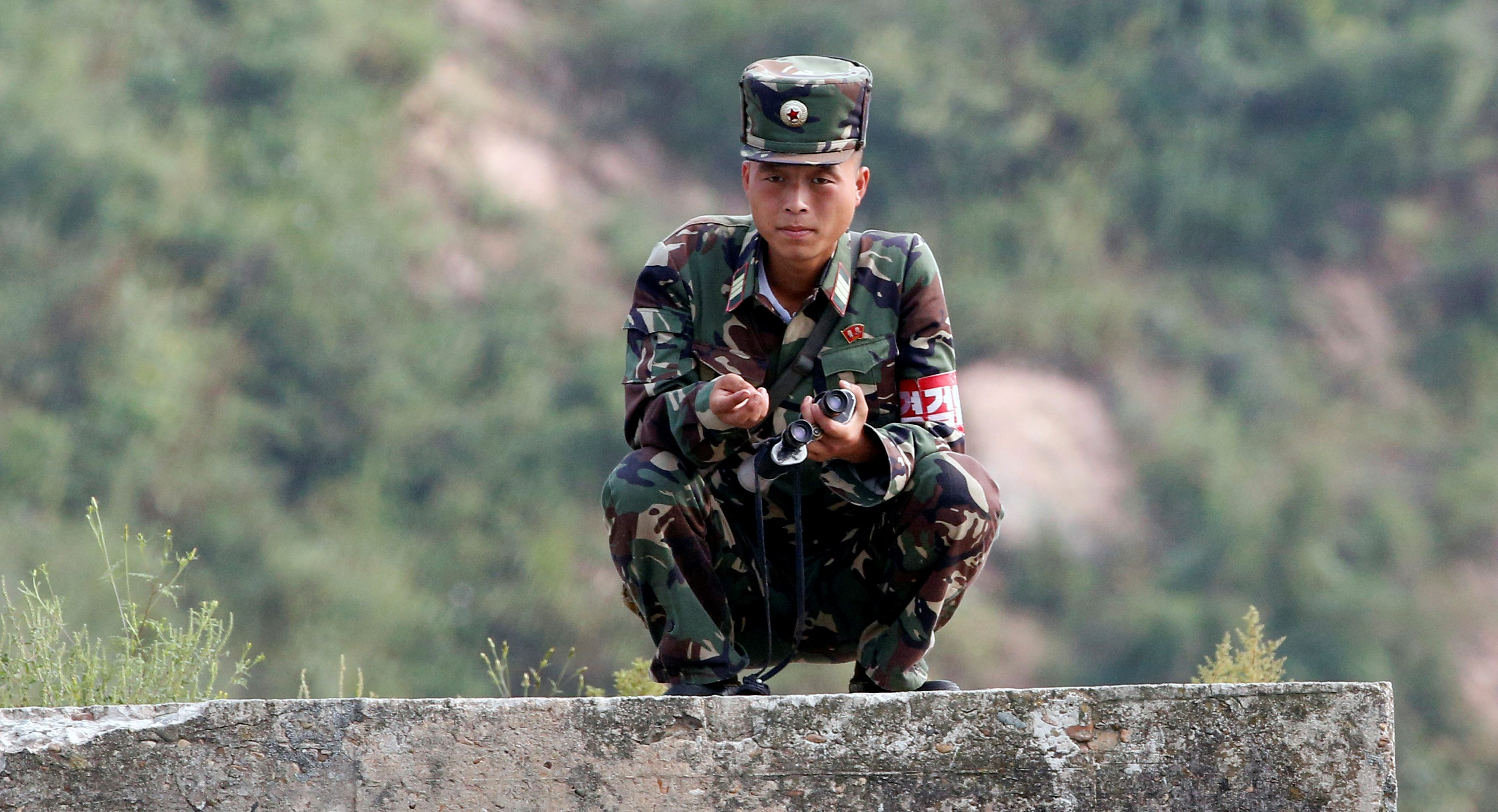 A North Korean soldier squats along the Yalu River in Sinuiju, North Korea, which borders Dandong in China's Liaoning province