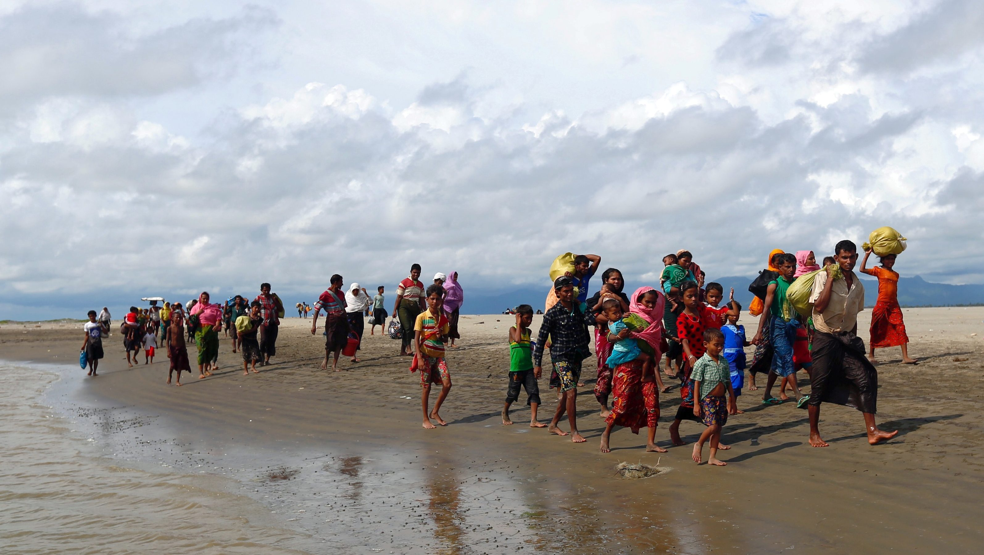 Rohingya refugees walk on the shore after crossing the Bangladesh-Myanmar border by boat through the Bay of Bengal in Shah Porir Dwip, Bangladesh September 11, 2017.