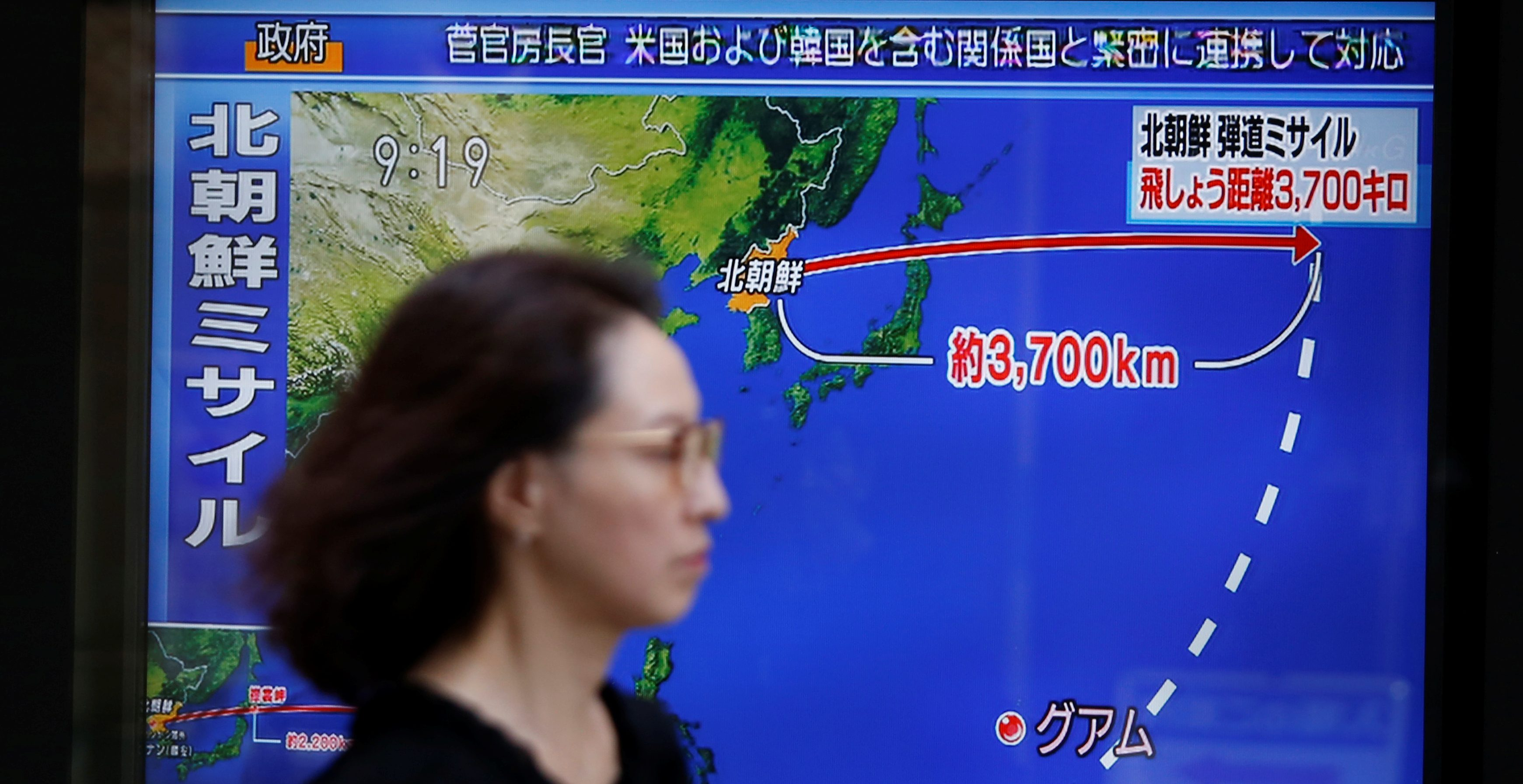 A passerby walks past a TV screen reporting news about North Korea's missile launch in Tokyo