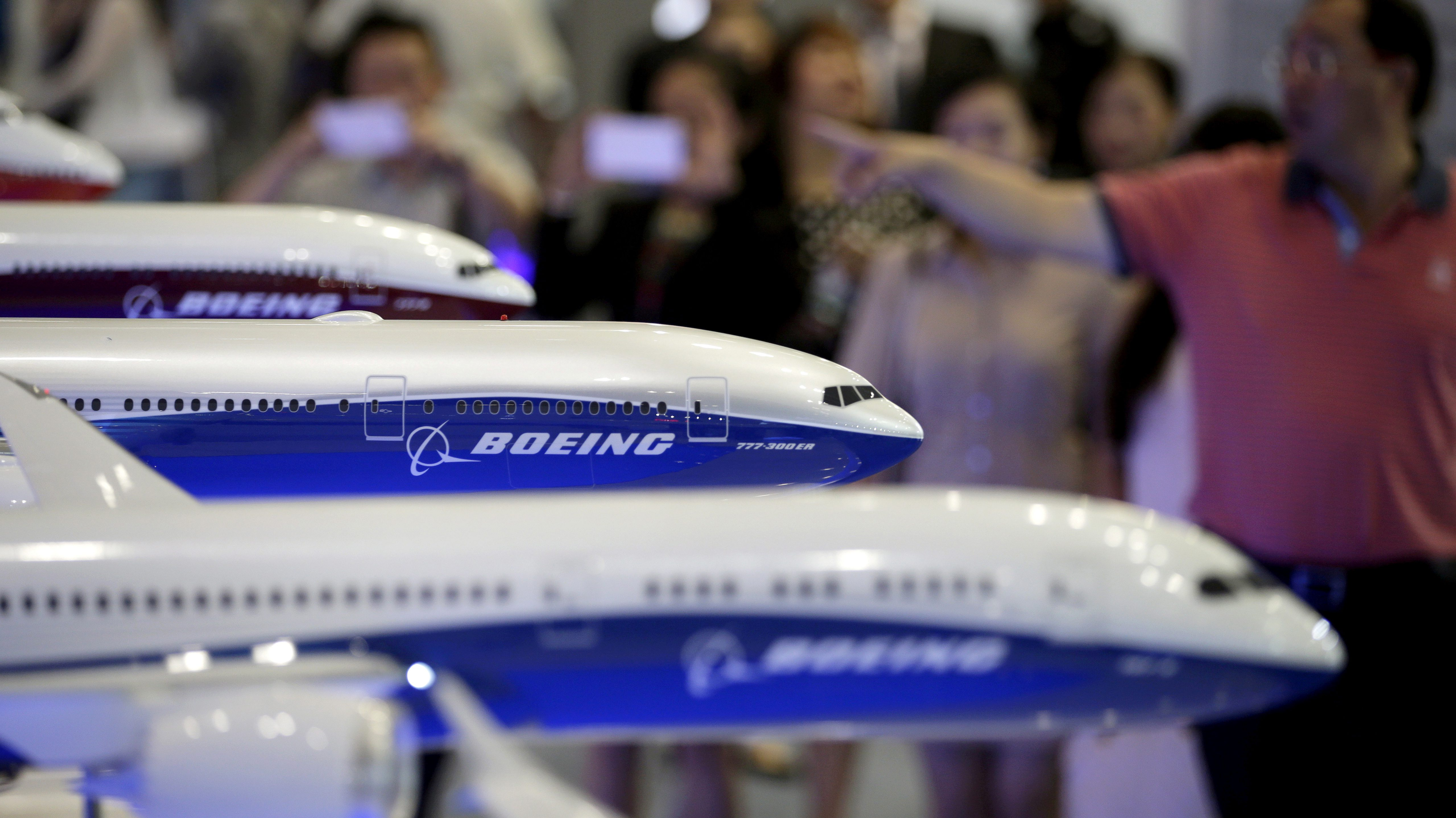 FILE PHOTO:  Visitors look at models of Boeing aircrafts at the Aviation Expo China 2015, in Beijing, China, in this September 16, 2015 file photo.   REUTERS/Jason Lee/File Photo - RC154B2ED010
