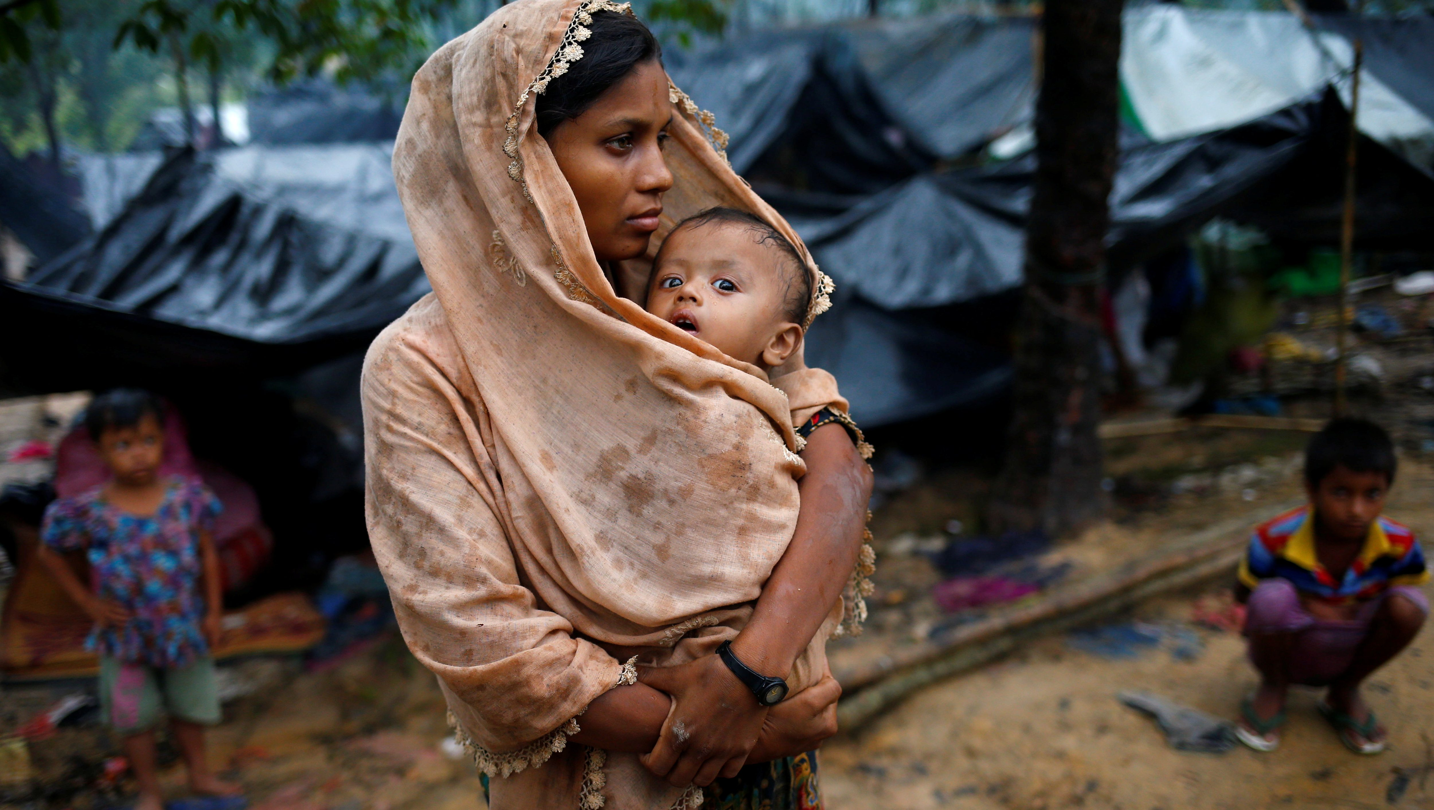 A Rohingya refugee woman wraps her child with a scarf as it drizzles in Cox's Bazar, Bangladesh, September 17, 2017.