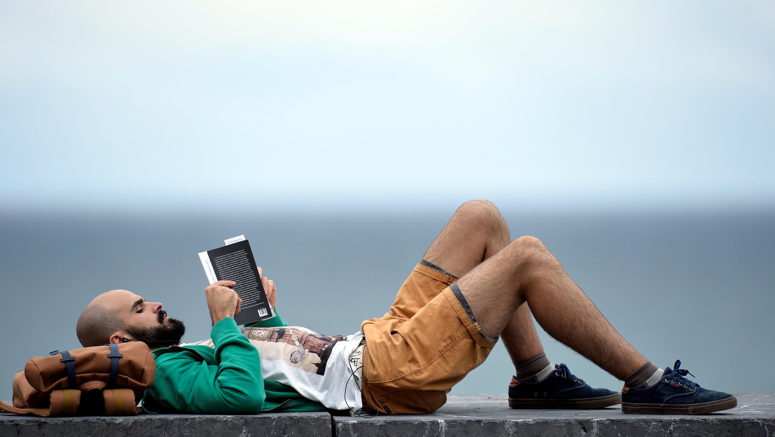 A man reads a book near a photocall at the San Sebastian Film Festival in San Sebastian, Spain, September 22, 2017. REUTERS/Vincent West - RC15570C3460
