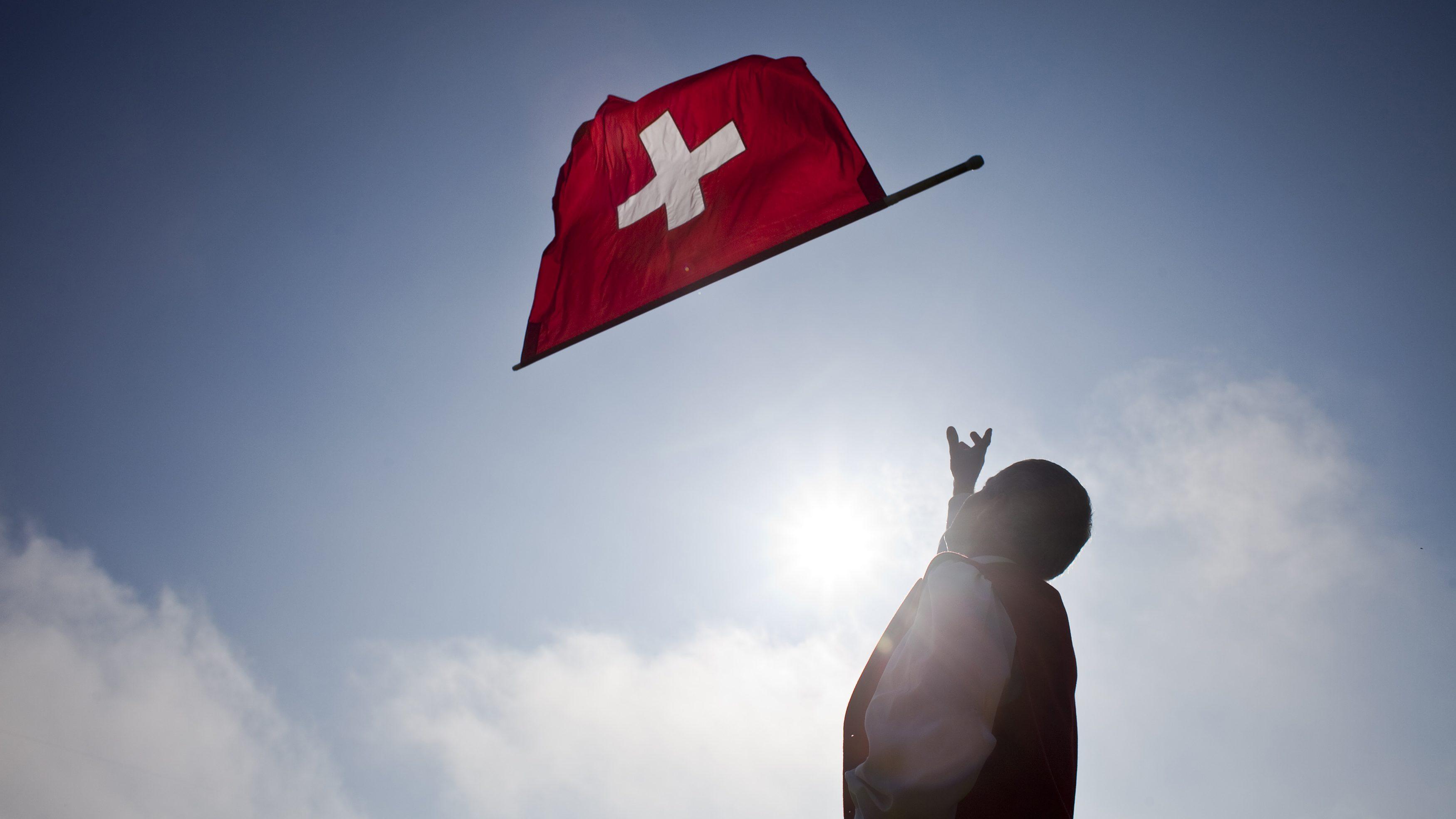 A man throws a Swiss national flag