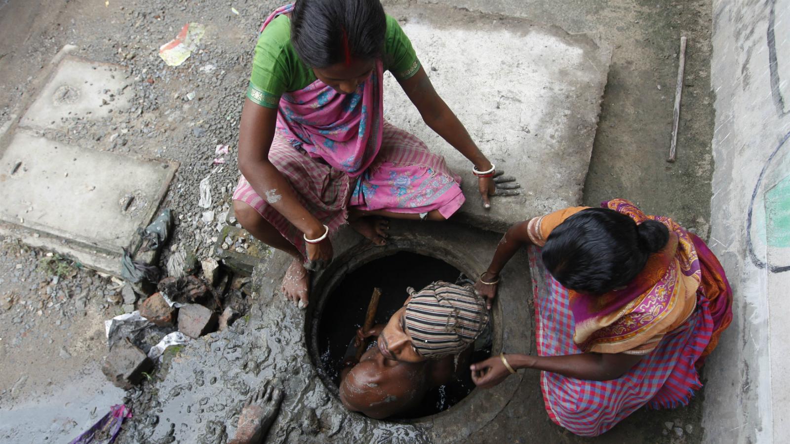 A labourer cleans an underground drain in Kolkata September 20, 2010.