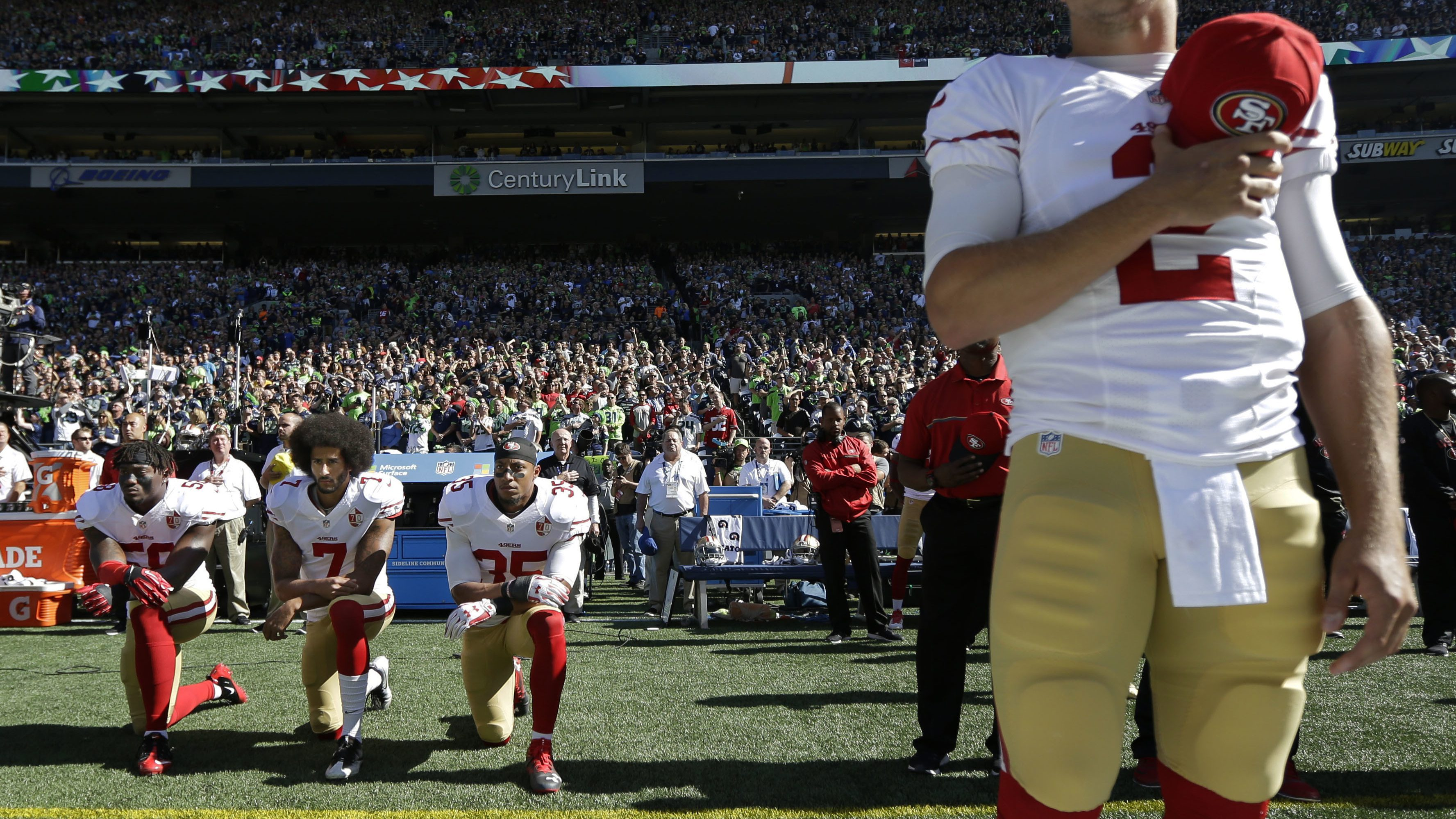 NFL San Francisco 49ers Eli Harold (58), Colin Kaepernick (7) and Eric Reid (35) kneel during the national anthem
