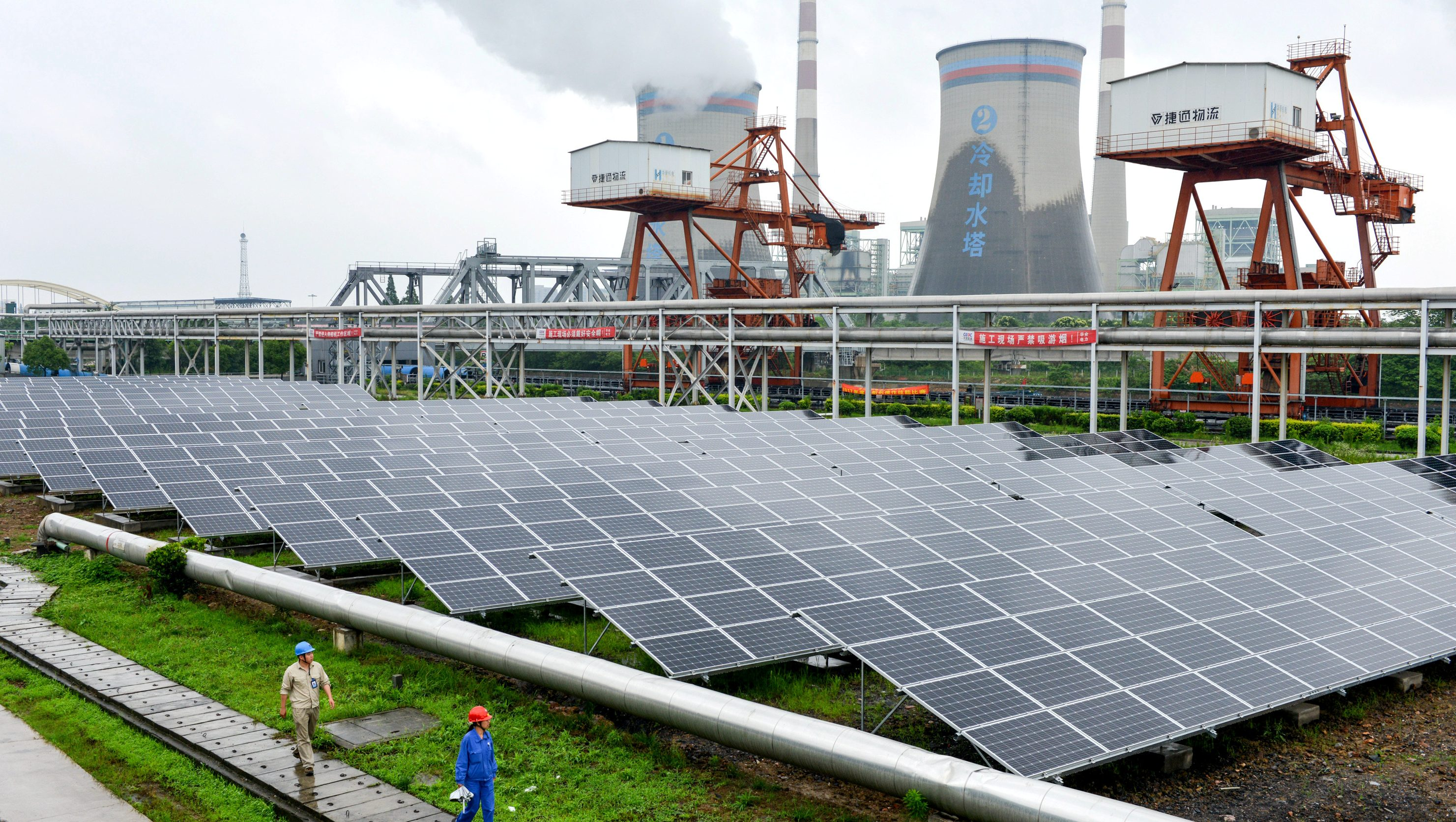 Employees check solar panels, as they work on a grid-connected photovoltaic power generation project, at a power plant in Changxing County, Zhejiang Province, China June 13, 2017.