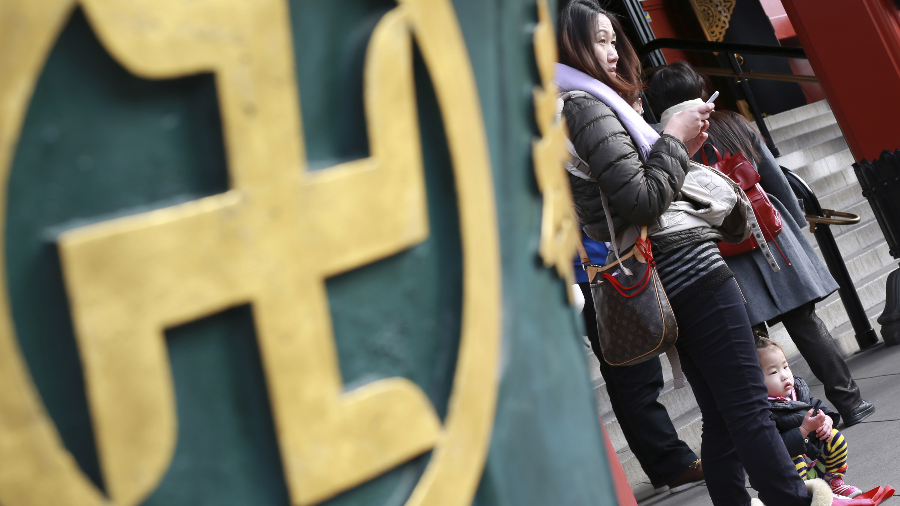 """In this Thursday, Feb. 3, 2016 photo, visitors stand next to a religious ornament with the """"manji"""" symbol, which comes from the ancient Sanskrit and is widely used for centuries to denote Buddhist temples on maps and elsewhere, at a temple in Tokyo. As Japan gears up to host the 2020 Tokyo Olympics and caters to a surging influx of foreign visitors, the country faces a cultural dilemma: Should it stop identifying Buddhist temples on maps with the traditional """"manji"""" symbol that is often confused with a Nazi swastika? (AP Photo/Eugene Hoshiko)"""