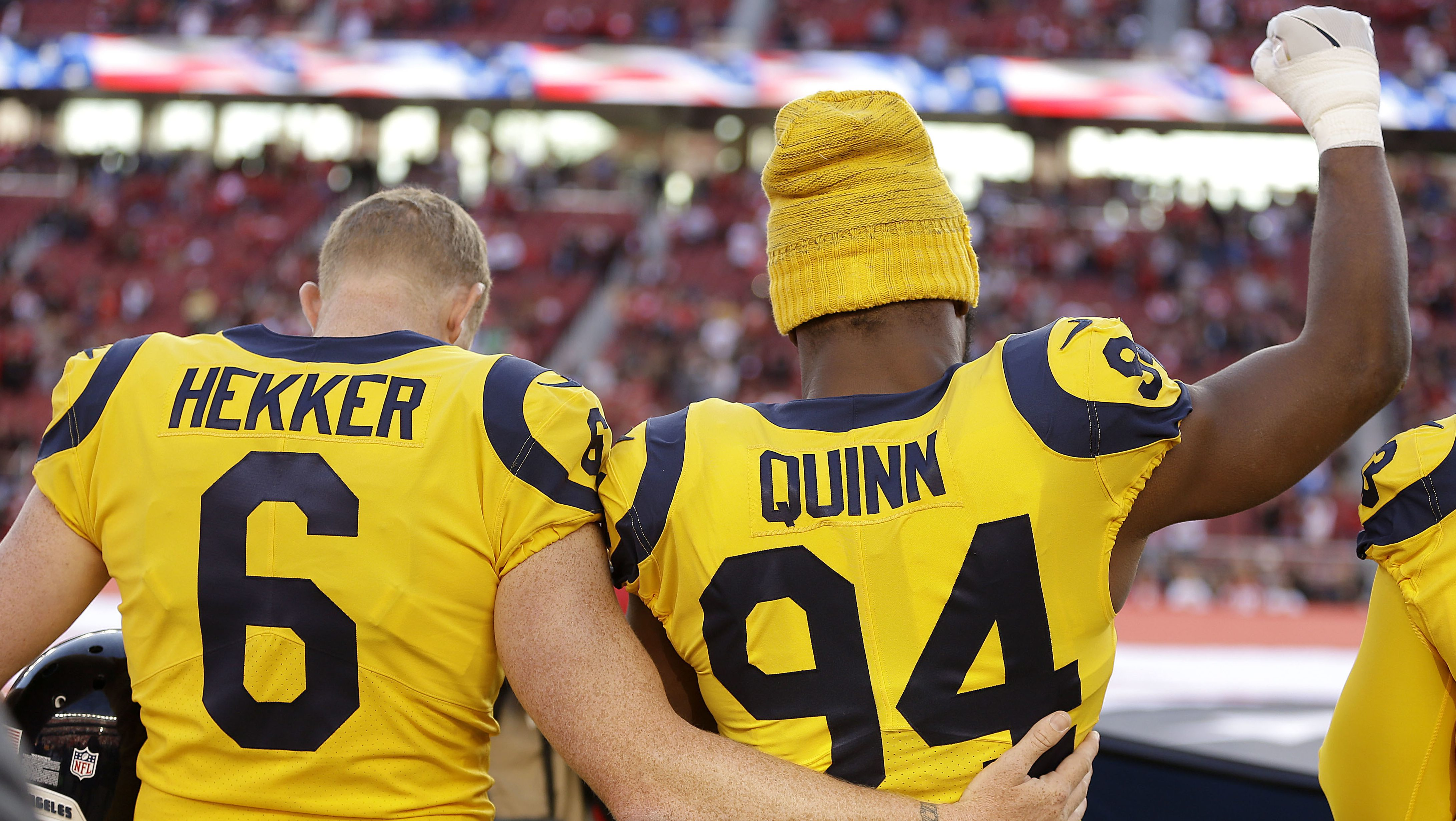 Los Angeles Rams punter Johnny Hekker (6) puts his arm around defensive end Robert Quinn (94) as he raises his fist during the performance of the national anthem before an NFL football game