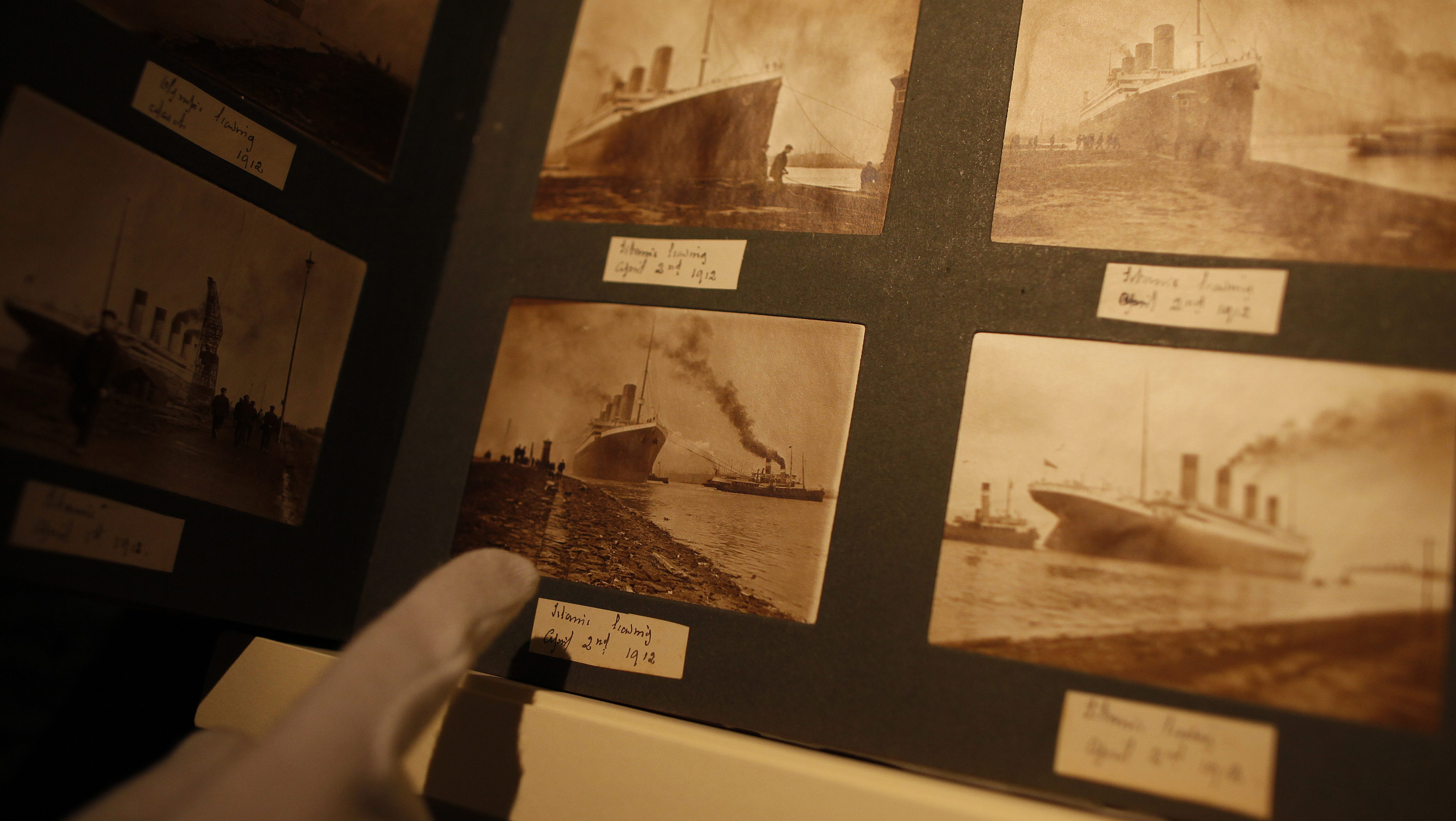 A member of staff at the Transport museum in Belfast, Northern Ireland, points to photographs of the Titanic displayed in a family album, Tuesday, Oct. 14, 2014. The album featuring never seen before pictures was displayed Tuesday which showed the launch and departure from Belfast in 1912. The album containing 116 prints belonged to John W Kempster who was a director and the master of ceremonies at Harland & Wolff, the Belfast shipyard that built the ship. (AP Photo/Peter Morrison)