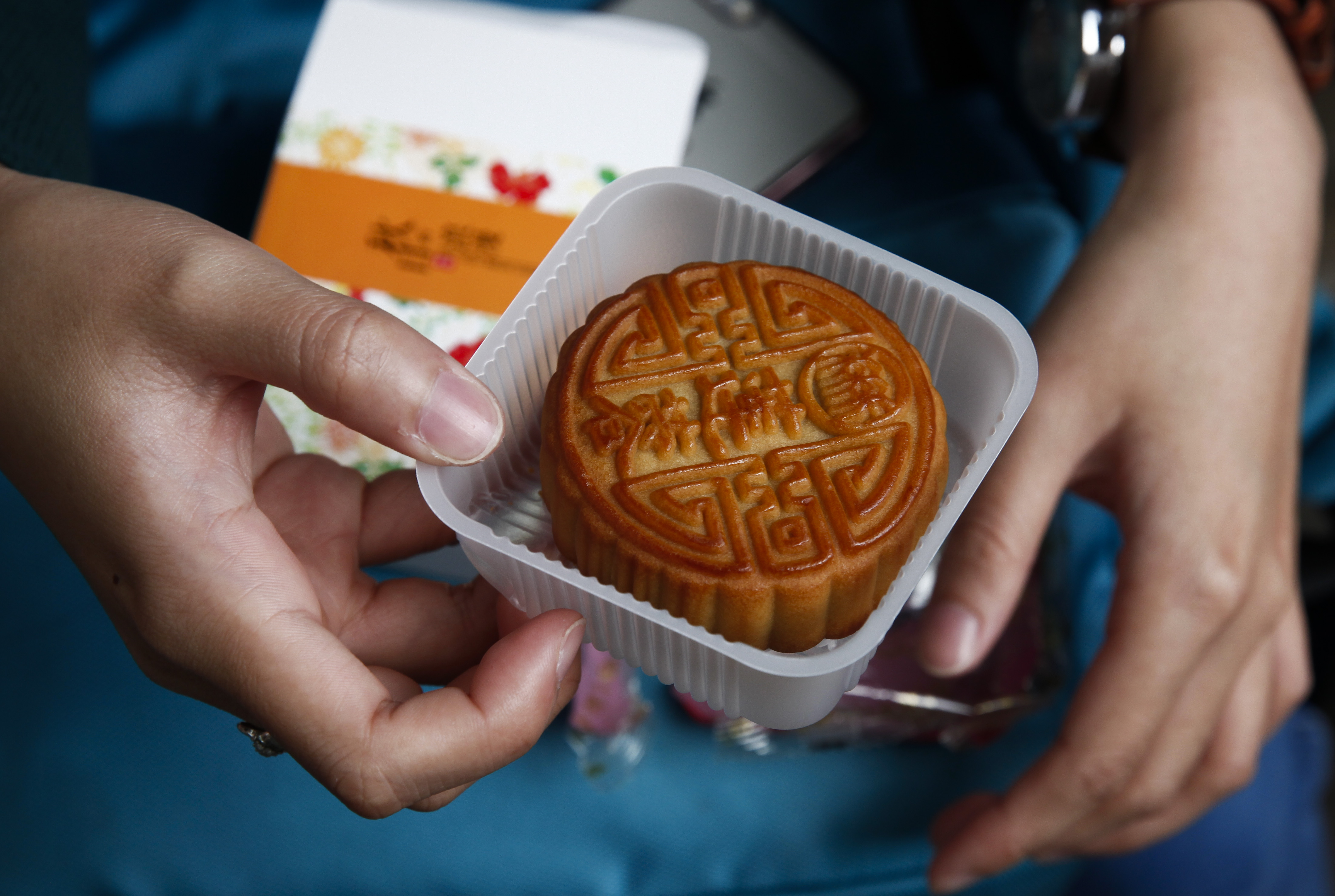 epa05540266 A college-level Indonesian student opens a box of mooncakes as part of an activity held to teach foreign students about the Mid-Autumn Festival at Jingshan Park in Beijing, China, 15 September 2016. China observes the Mid-Autumn Festival or Mooncake Festival on 15 September, which this year is the 15th day of the eighth month in the lunar calendar where traditionally family members and friends gather to admire the mid-autumn moon and eat moon cakes together.