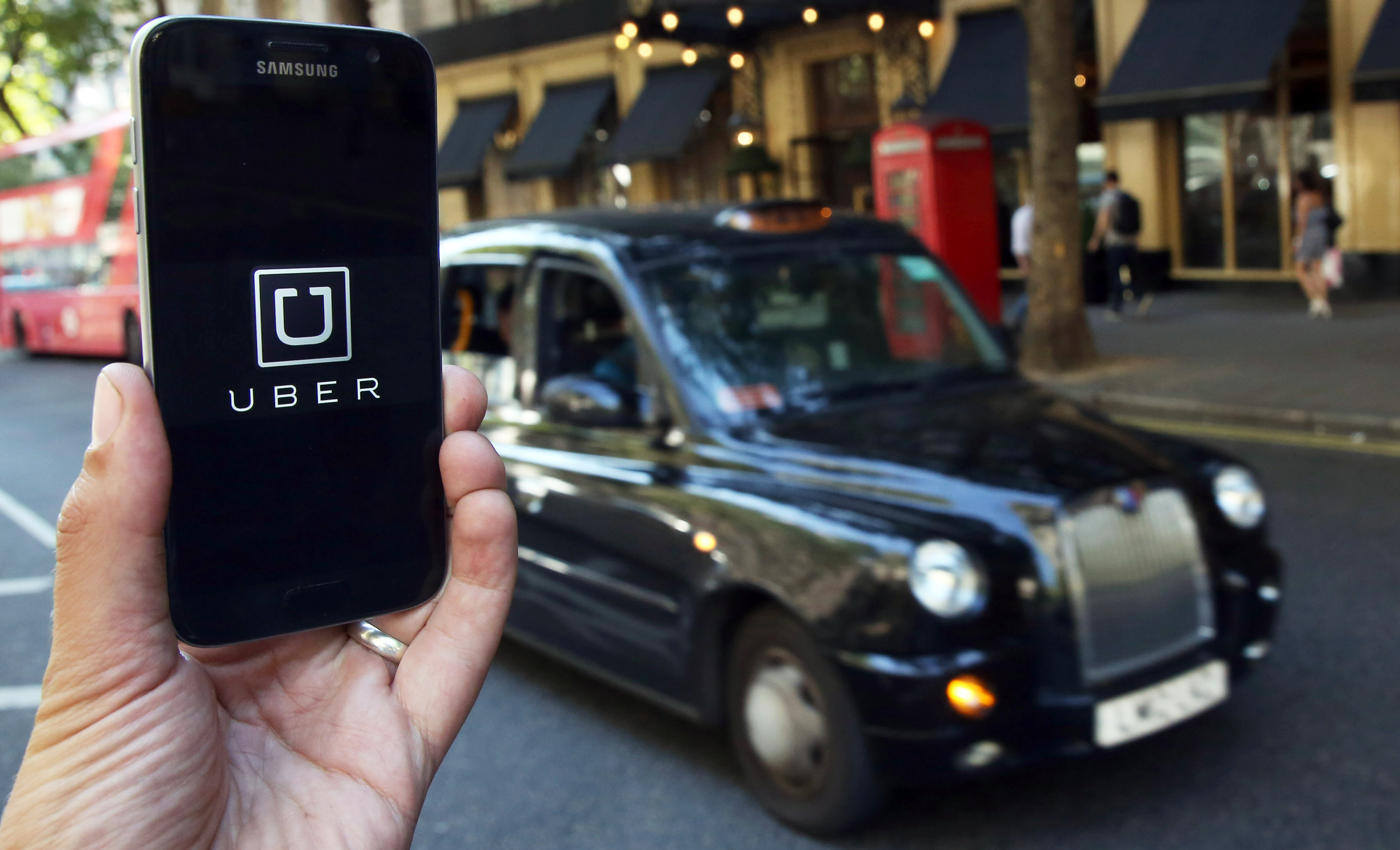 A photo illustration shows the Uber app logo displayed on a mobile telephone, as it is held up for a posed photograph in central London, Britain August 17, 2016. This logo has been updated and is no longer in use.