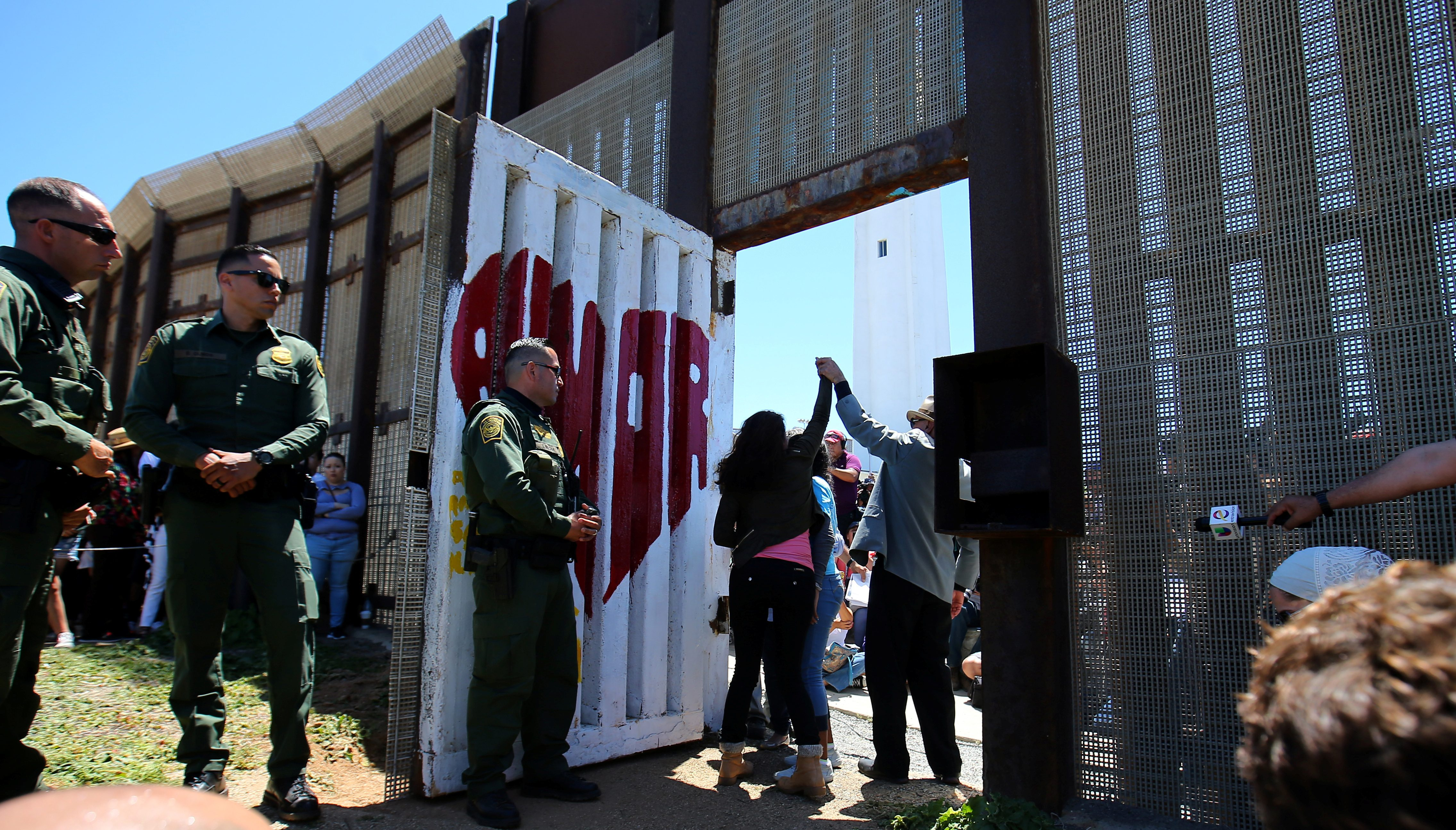 A family celebrates as U.S. Border patrol agents open a single gate to allow selected families to hug along the Mexico border