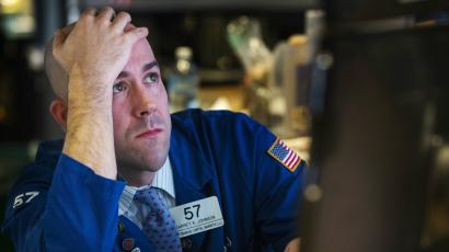 A trader watches the screen at his terminal on the floor of the New York Stock Exchange