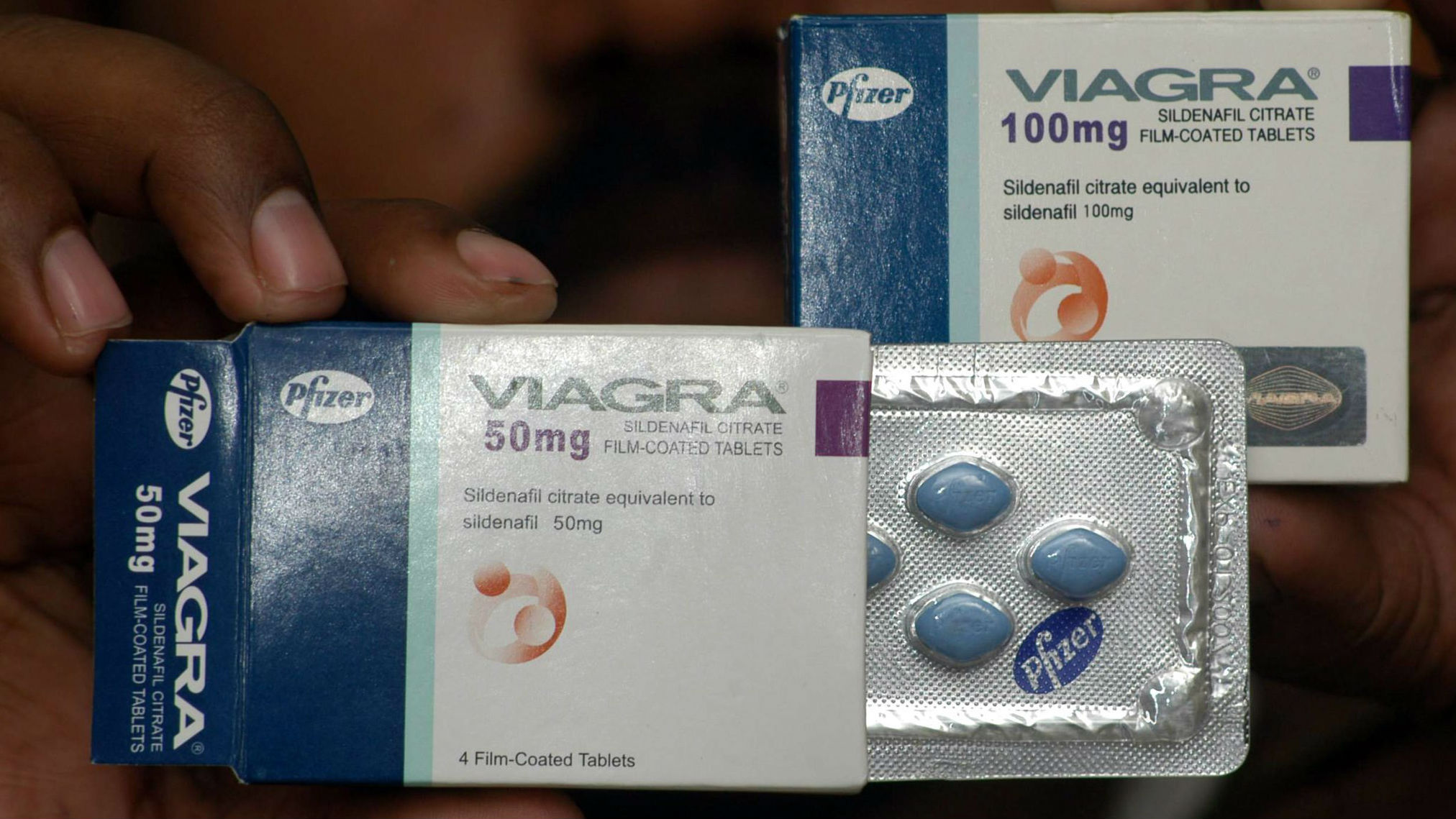 A hand holding a box of Viagra with some of the wrapped pills exposed.